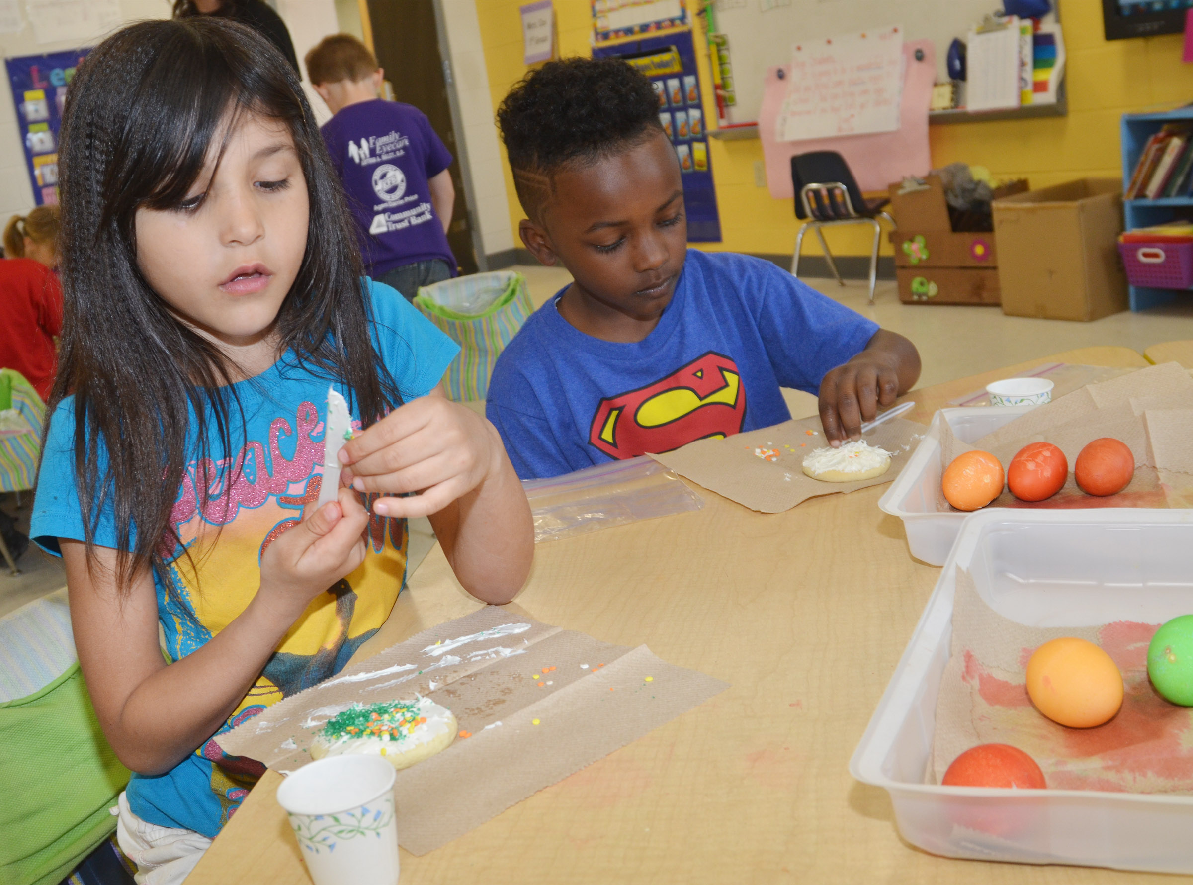 CES first-graders Gemma Bledsoe, at left, and Drelynn Hollins decorate their cookies.
