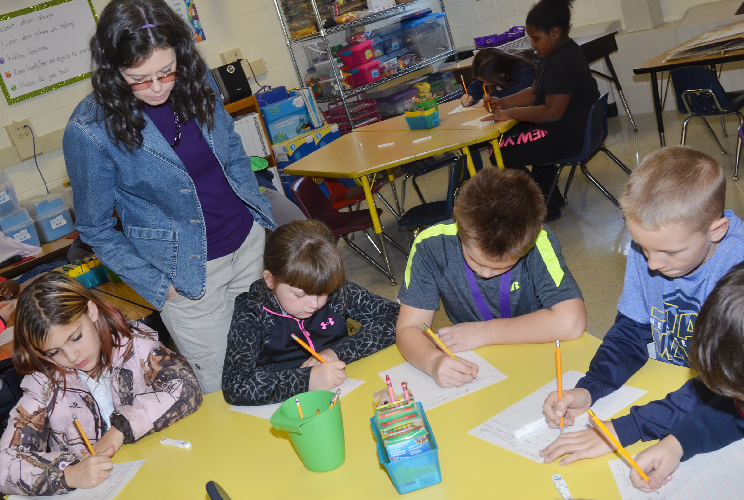 CES writing teacher Shirley Cox watches as third-graders write about gingerbread houses.