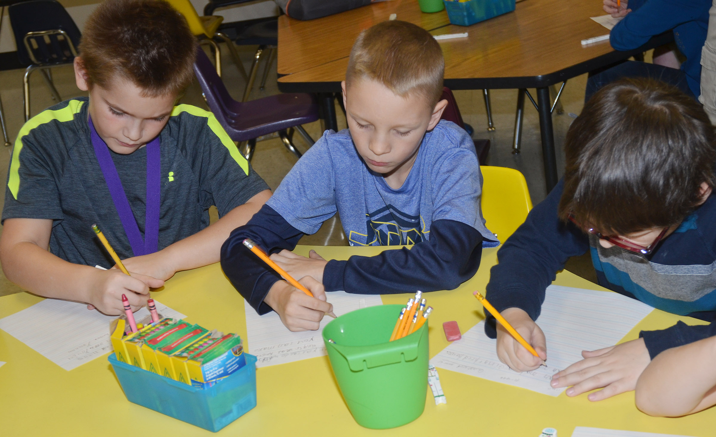 From left, CES third-graders Sean Welch, Braxton Agee and Cobain Carter write about gingerbread houses.