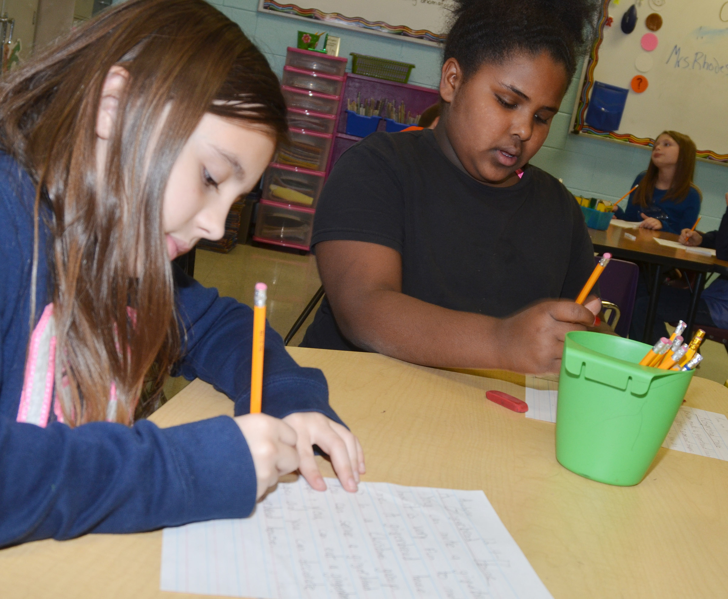 CES third-graders Annabelle Brockman, at left, and Ajada Smith write about gingerbread houses.