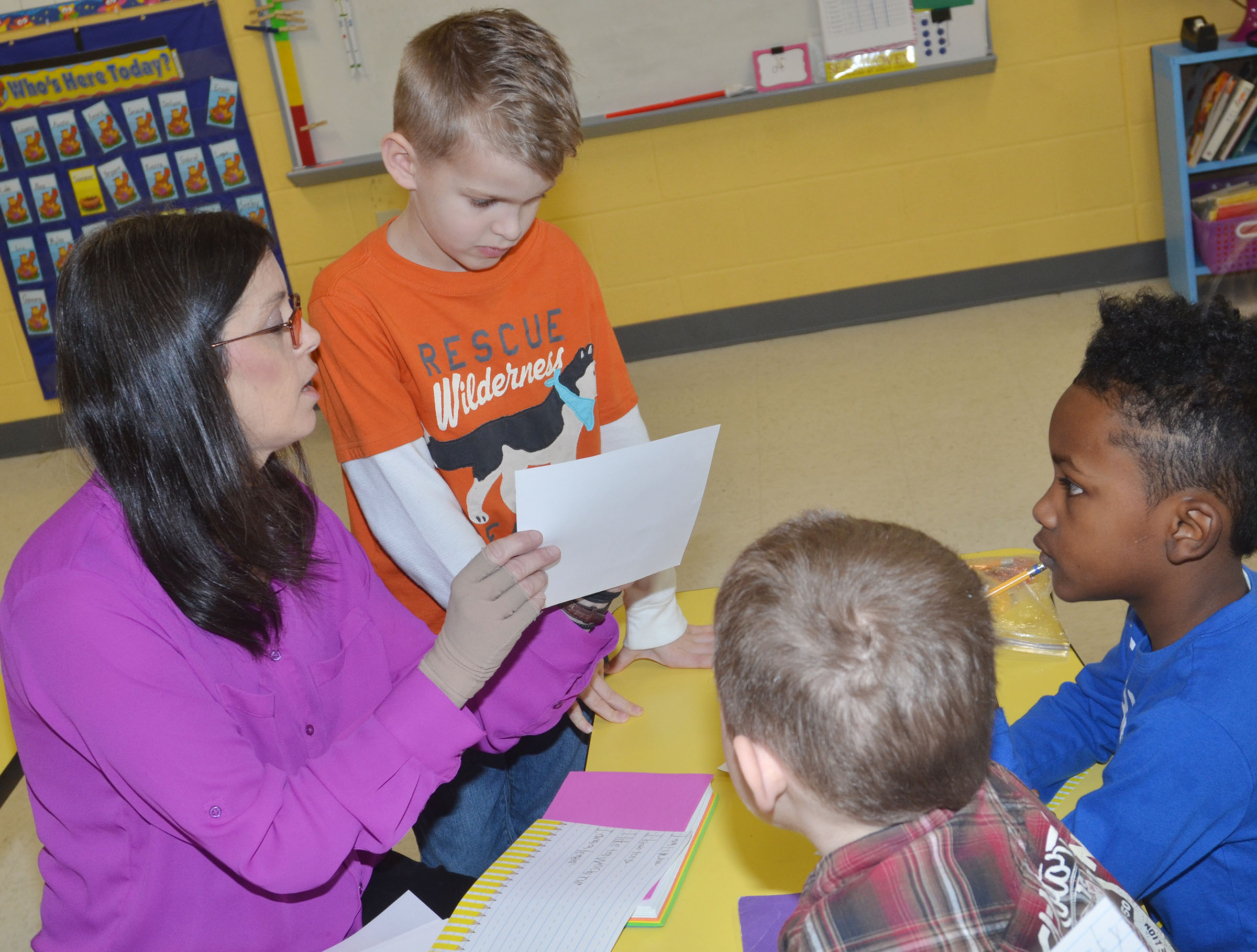CES first-grade teacher Shirley Cox helps Logan Weddle with his writing.