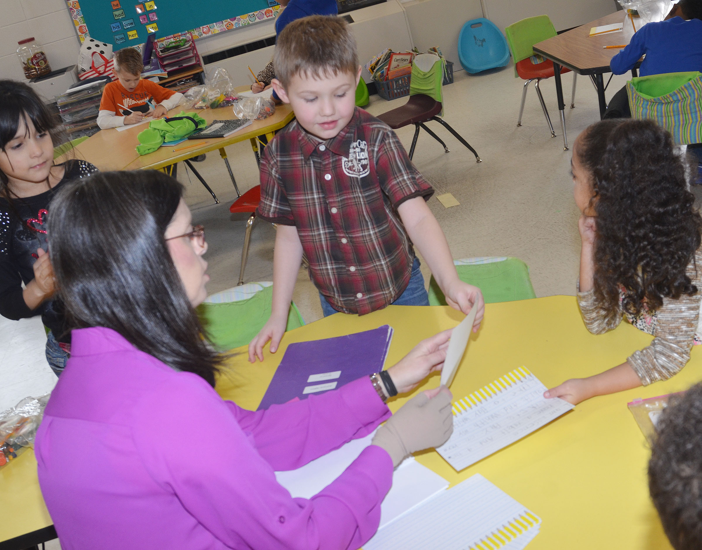 CES first-grade teacher Shirley Cox helps Lucian Abel with his writing.