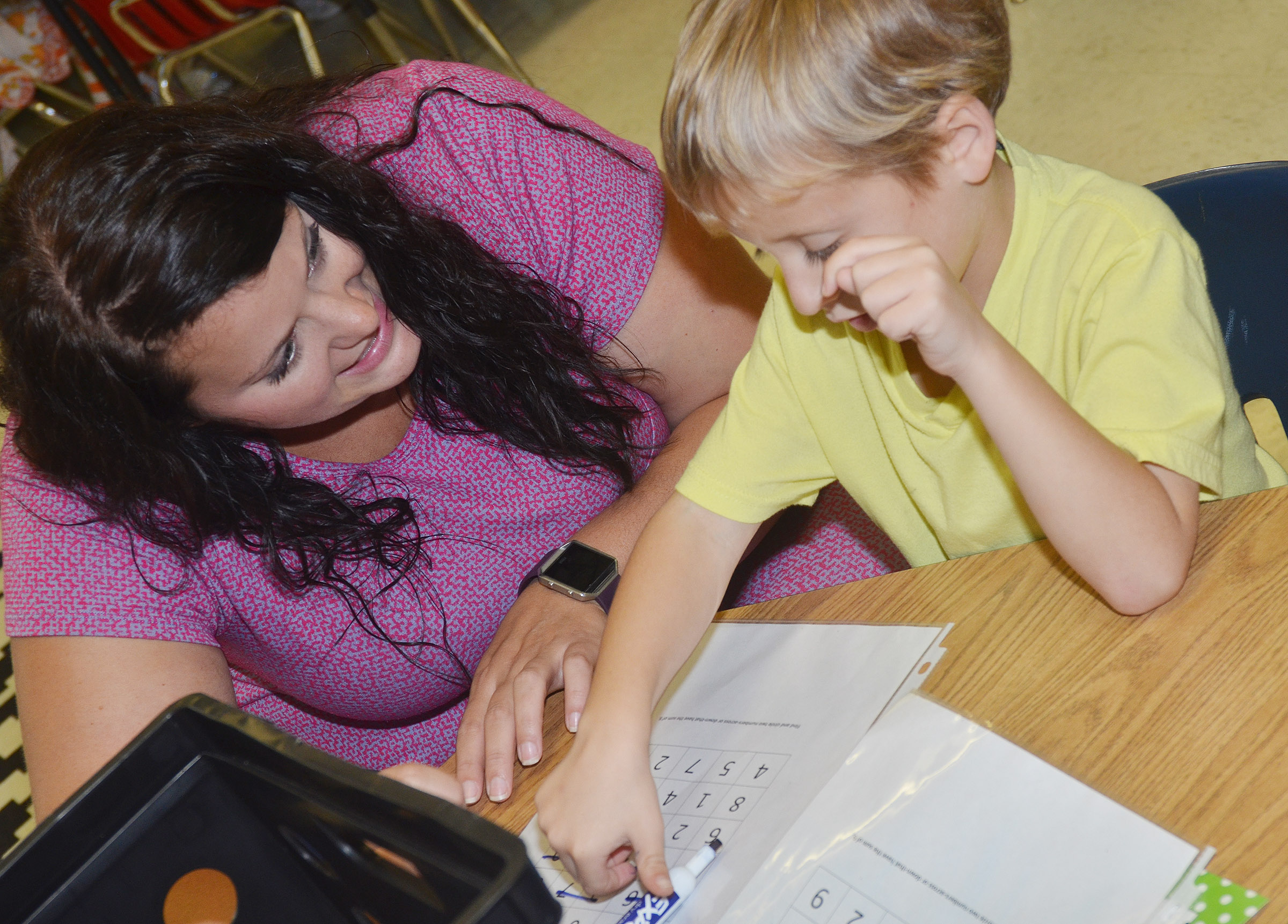 CES first-grade teacher Miriah Cox helps Gavin Paris find numbers that add to make 10.