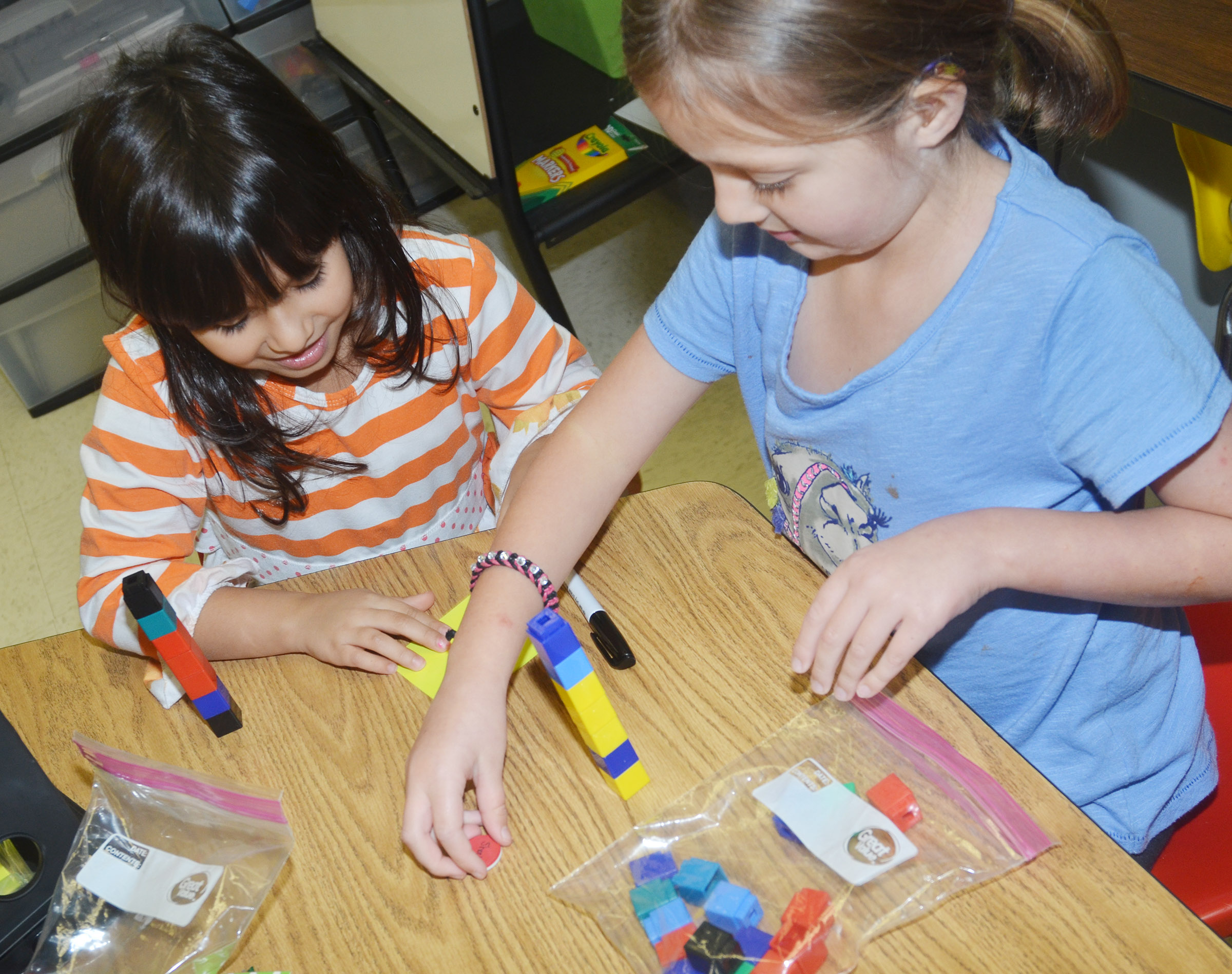 CES first-graders Carol Moura, at left, and Delaney Staton count blocks together.
