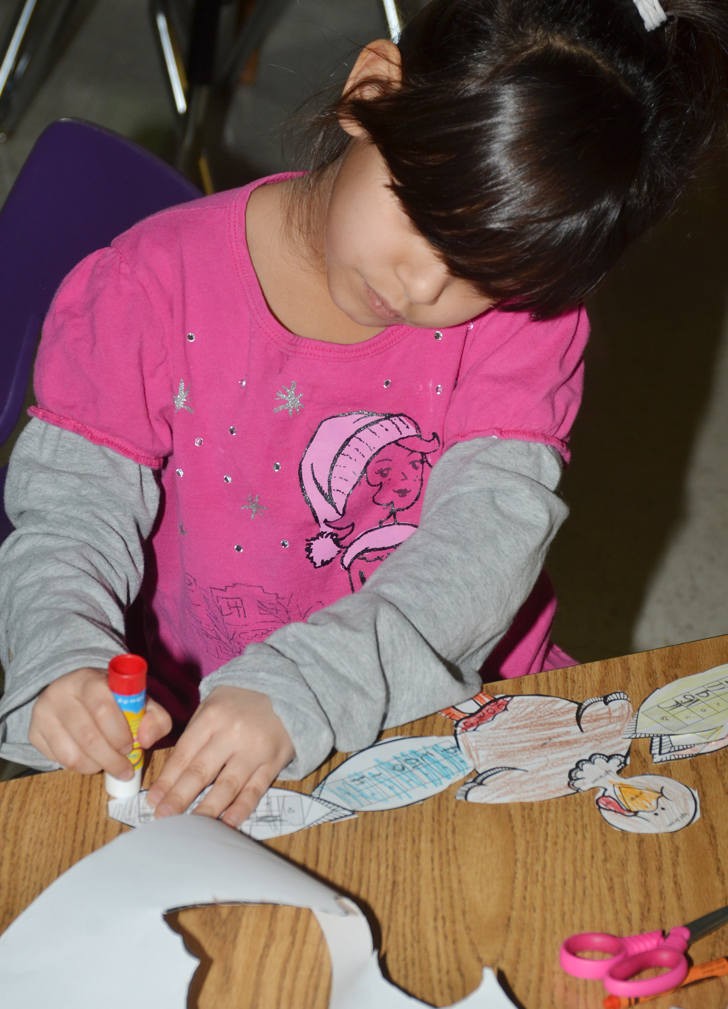 CES first-grader Carol Moura glues her feathers together after completing her math problems.