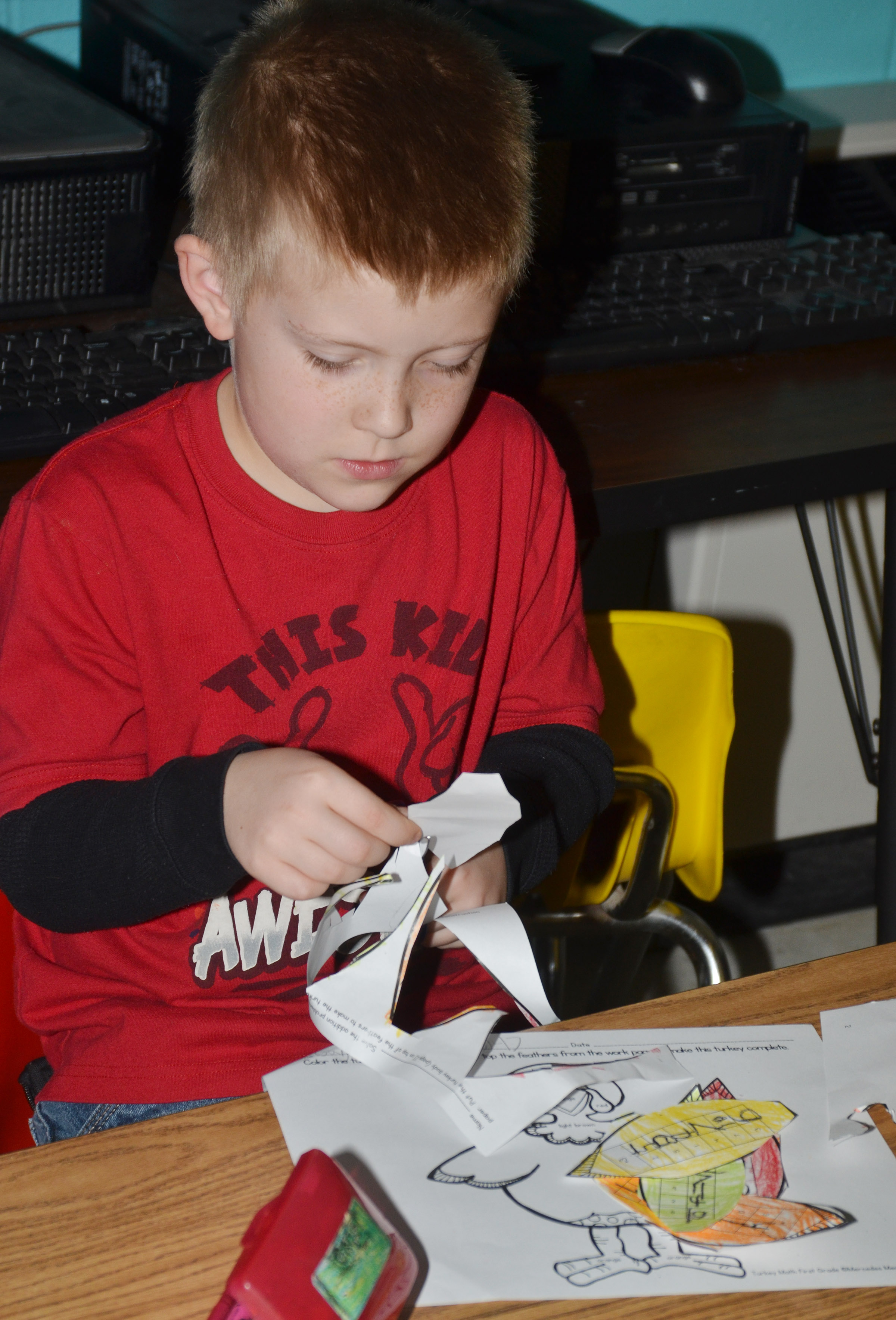 CES first-grader Gage Henderson cuts out his feathers.