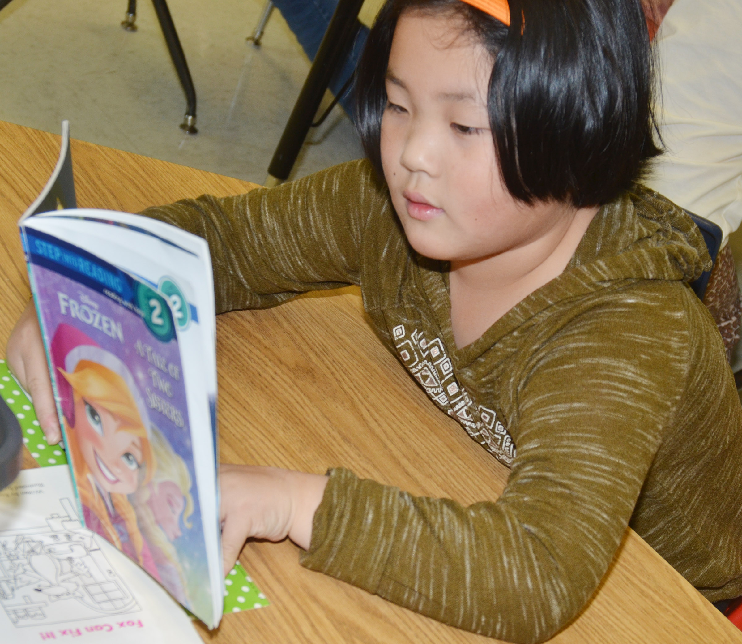 CES first-grader Vicky Li reads a chapter book.