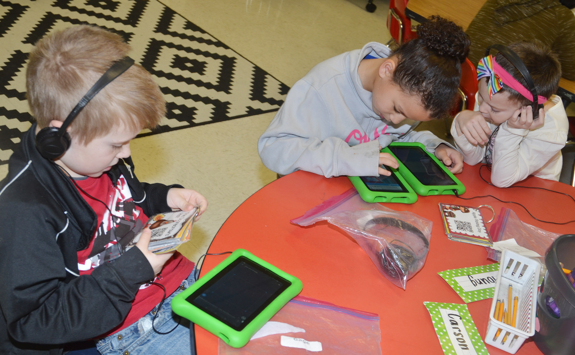 CES first-grader Gage Henderson, at left, reads with flashcards as his classmates Aleeya Spaulding and Madison Haywood read together on a tablet.