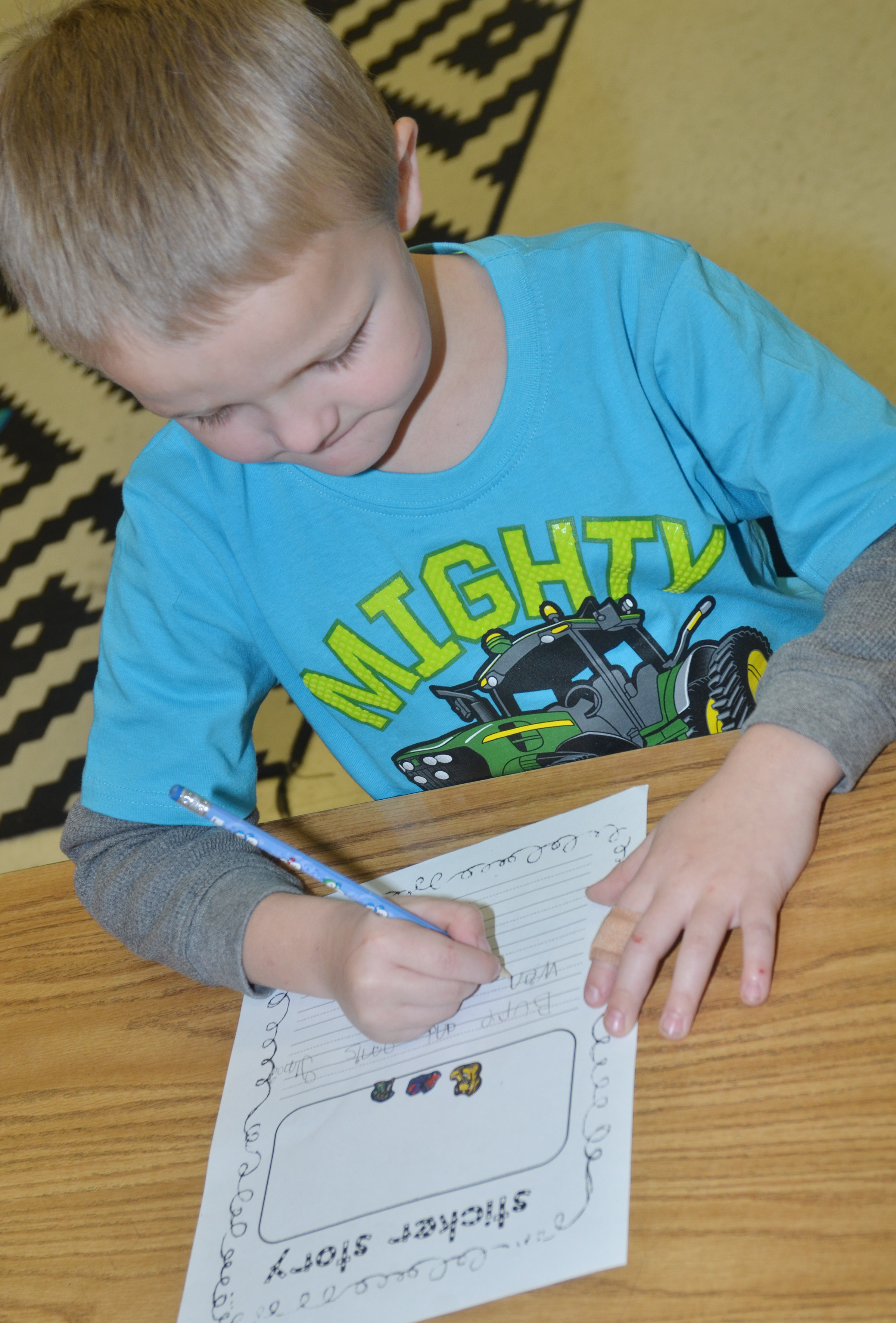 CES first-grader Tristian Harris writes about the story he created by using stickers.