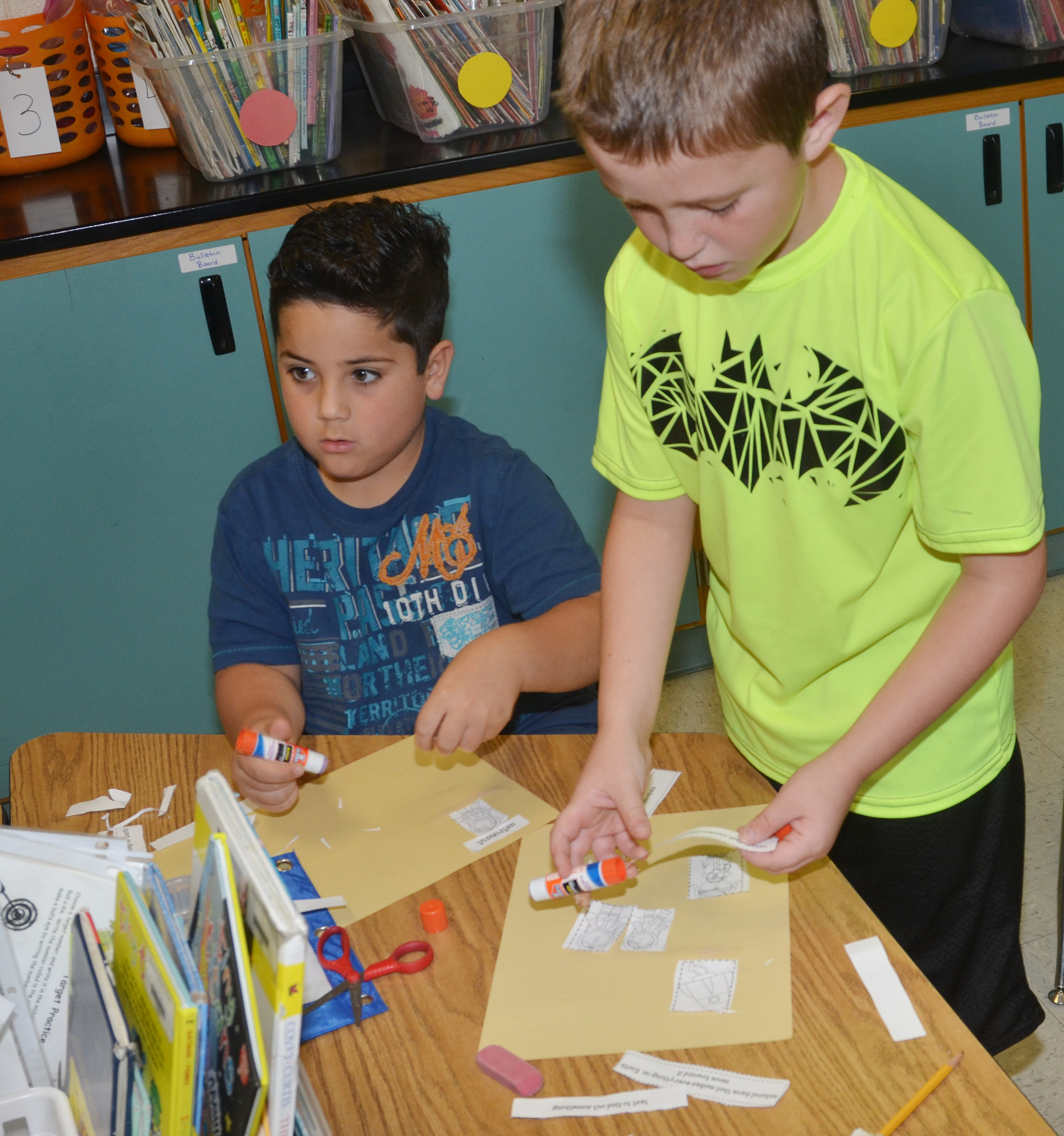 CES second-graders Nicholas Almeida, at left, and Kevin Bradfield glue their space definitions on construction paper.