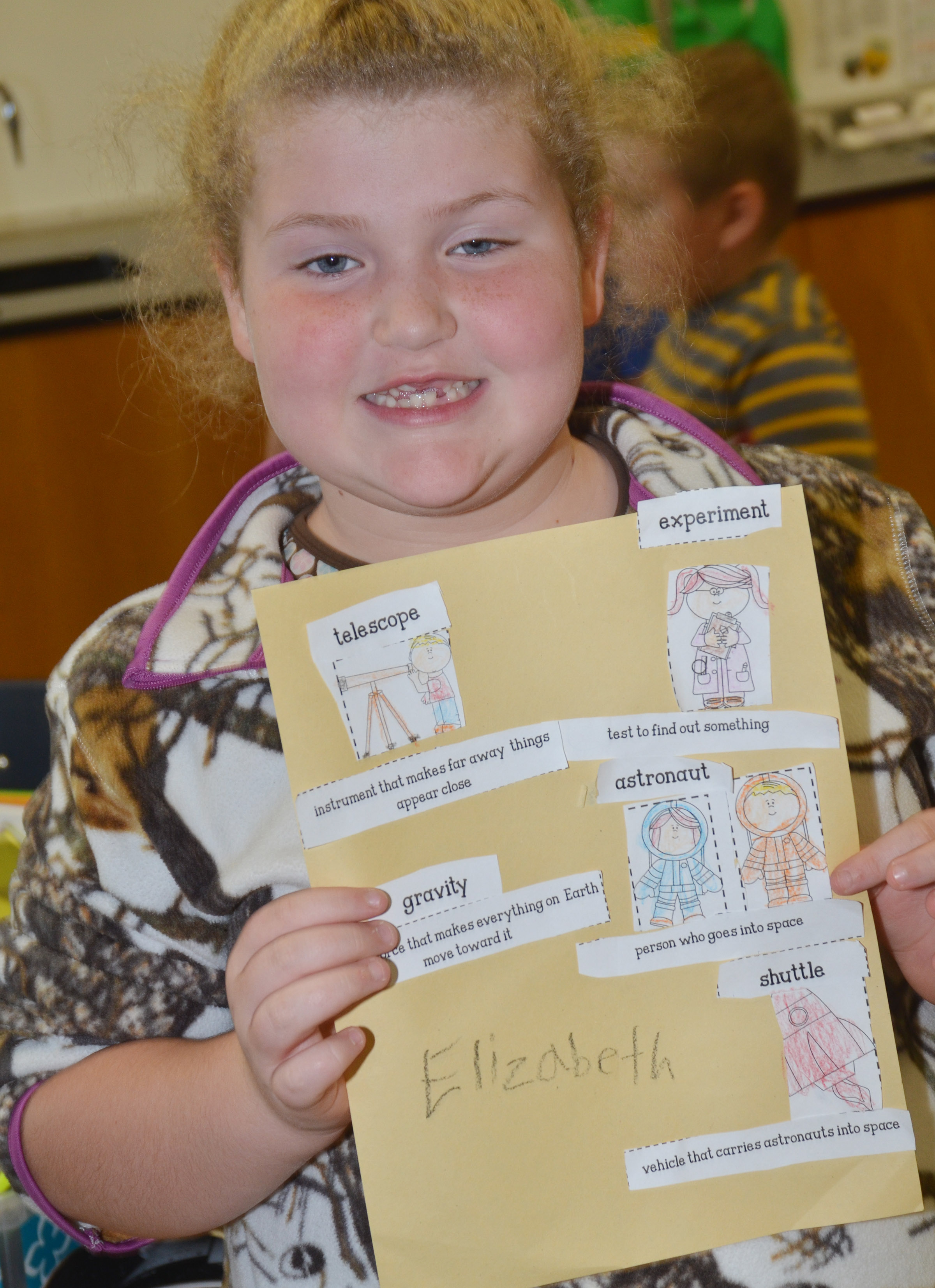 CES second-grader Elizabeth Foster holds her finished space vocabulary sheet.