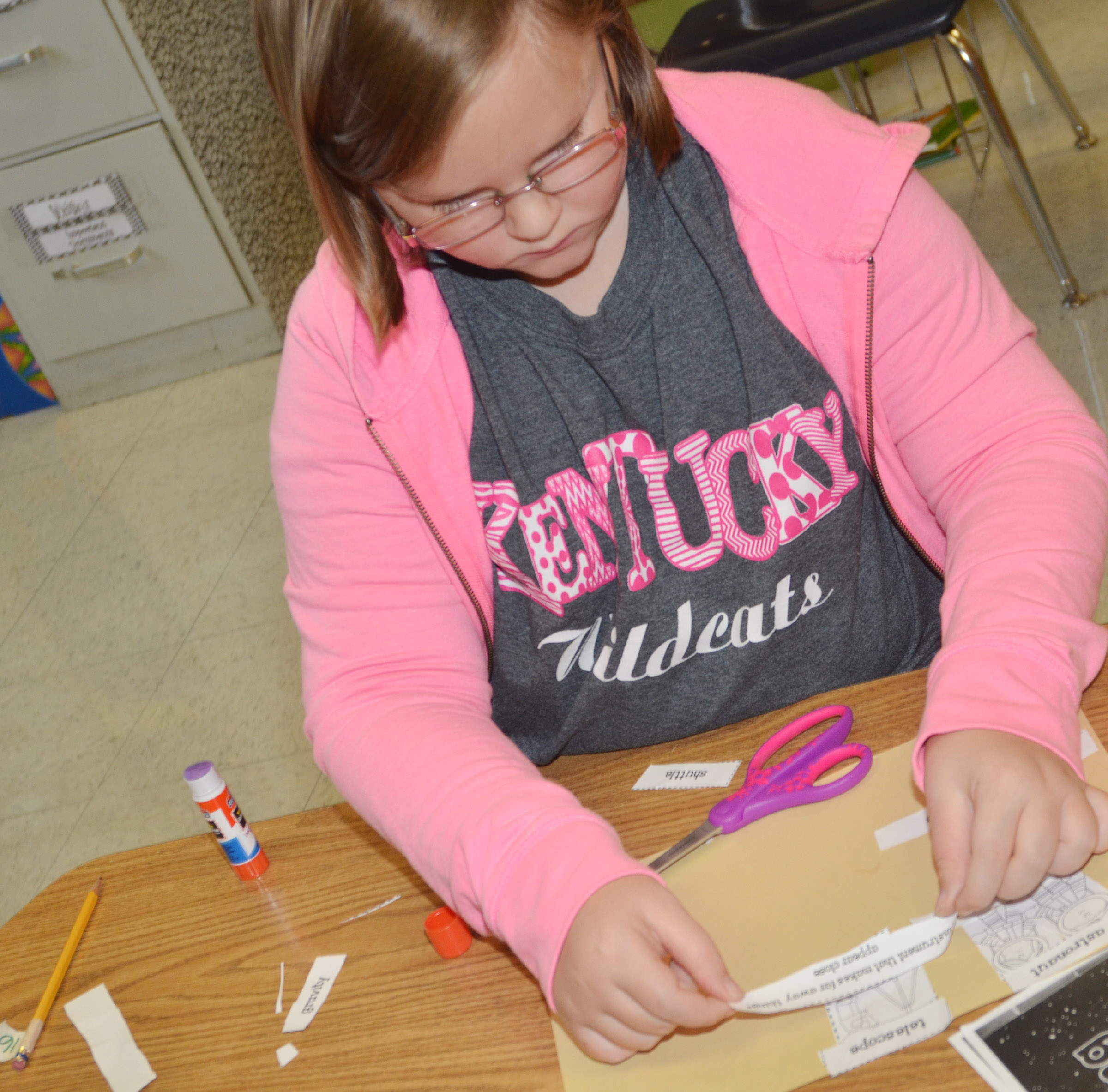 CES second-grader Justice Albrecht glues her space definitions with her vocabulary words.