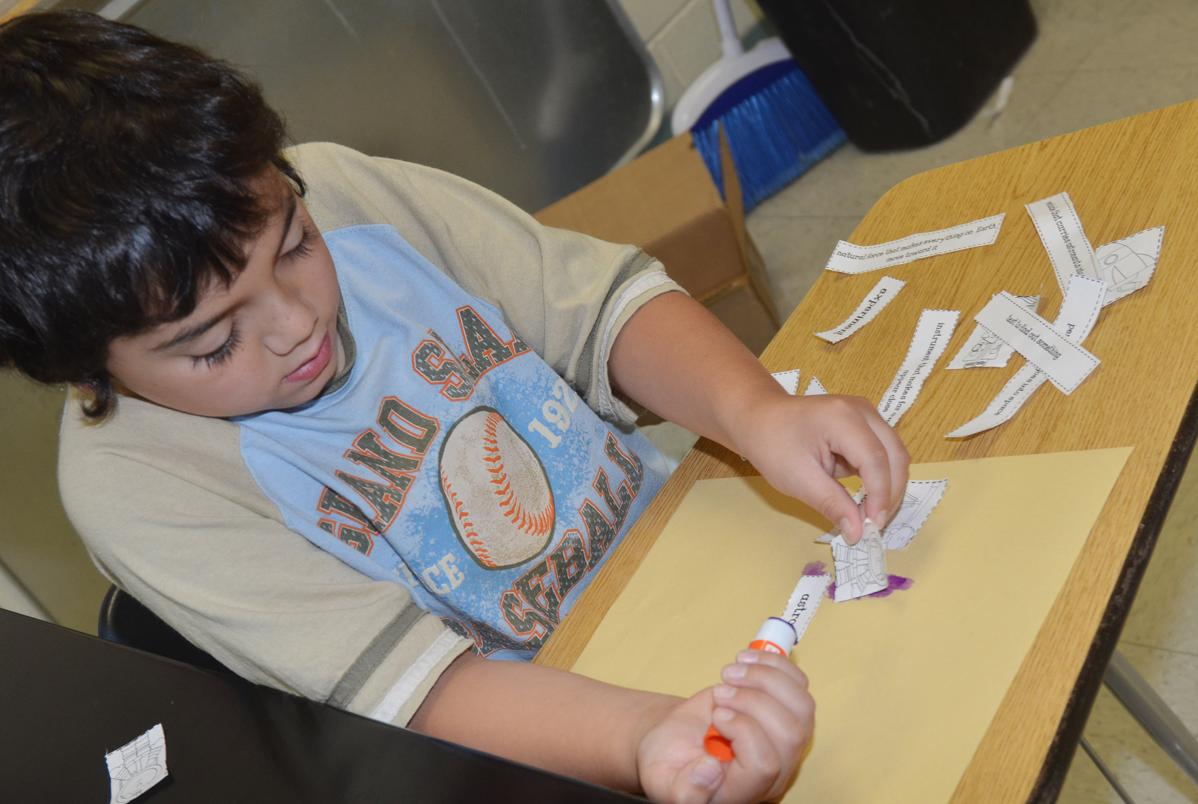 CES second-grader Diego Aquino glues his space definitions with his vocabulary words.
