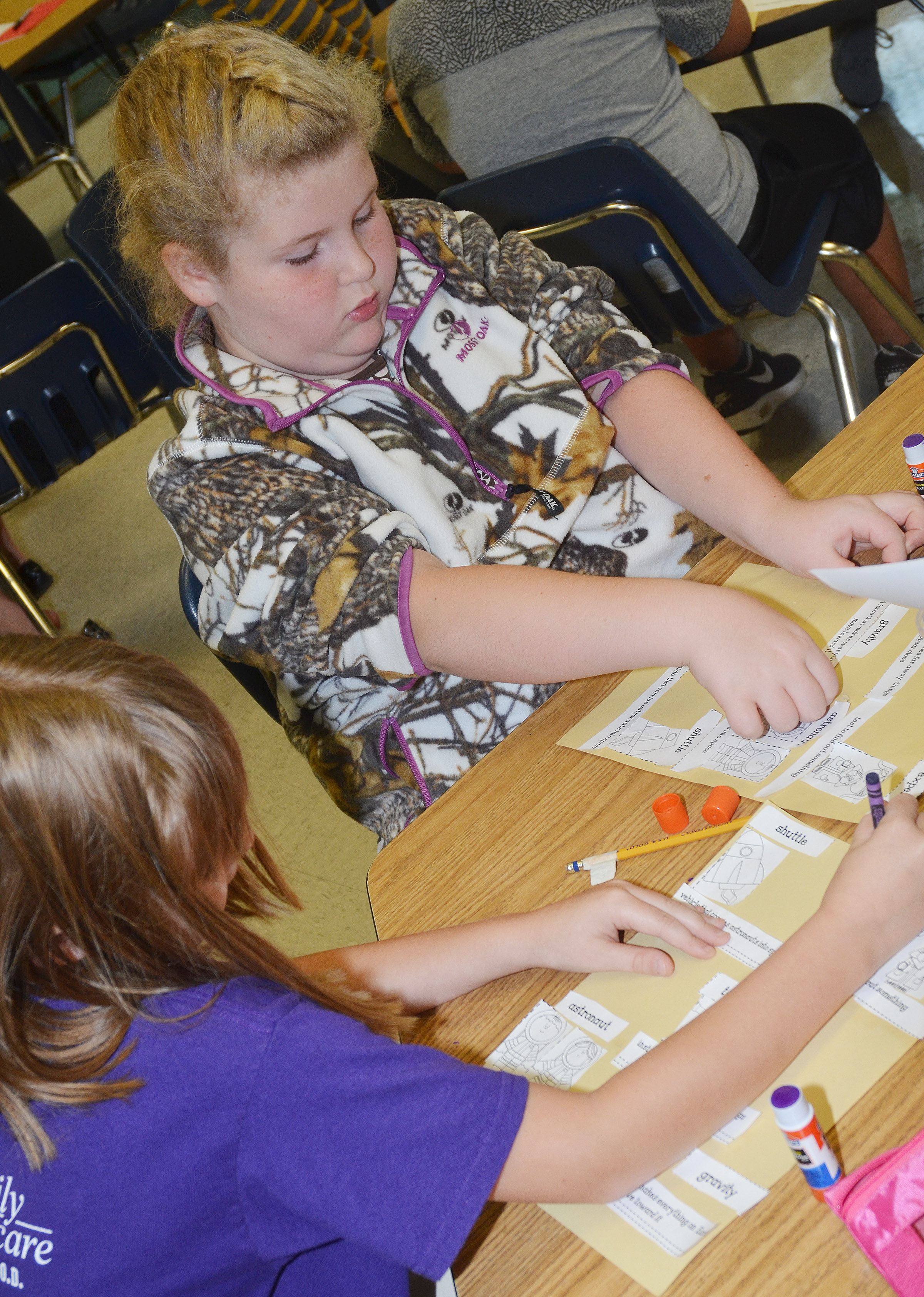 CES second-graders Gracie Murphy, at left, and Elizabeth Foster glue their space definitions with their vocabulary words.