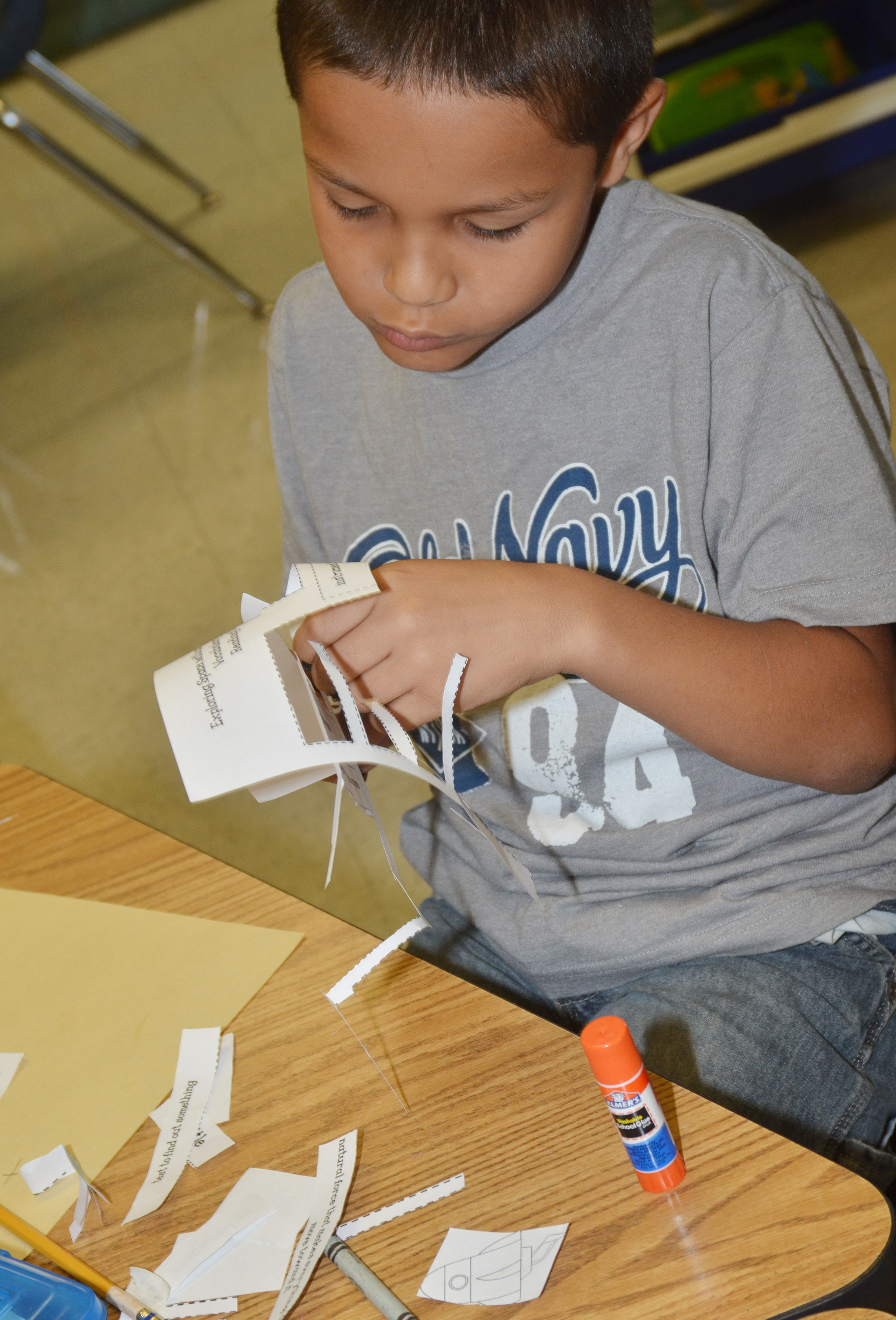 CES second-grader Makyian Bridgewater cuts out his space definitions to glue on his construction paper.