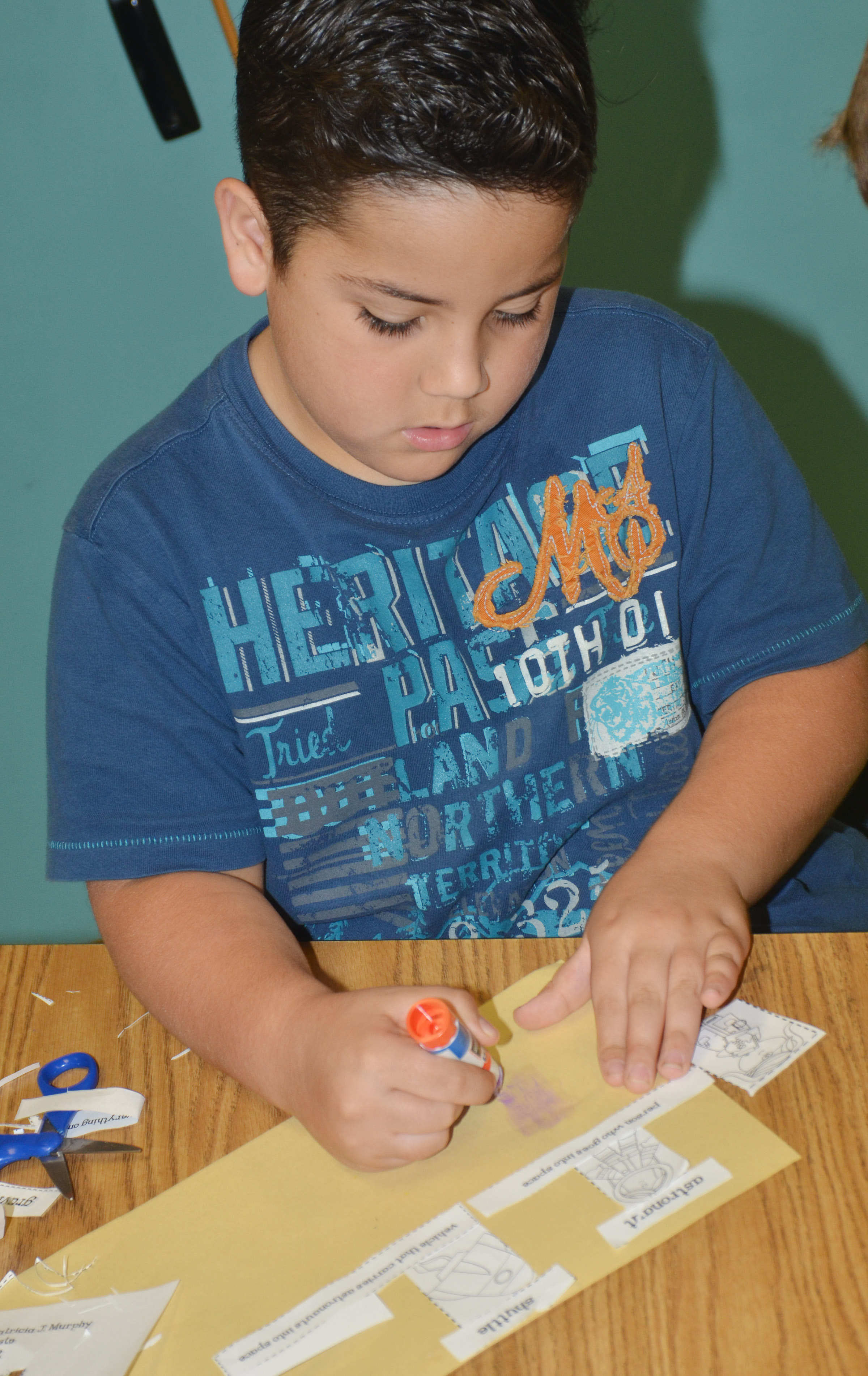 CES second-grader Nicholas Almeida glues his space vocabulary words with their definitions.