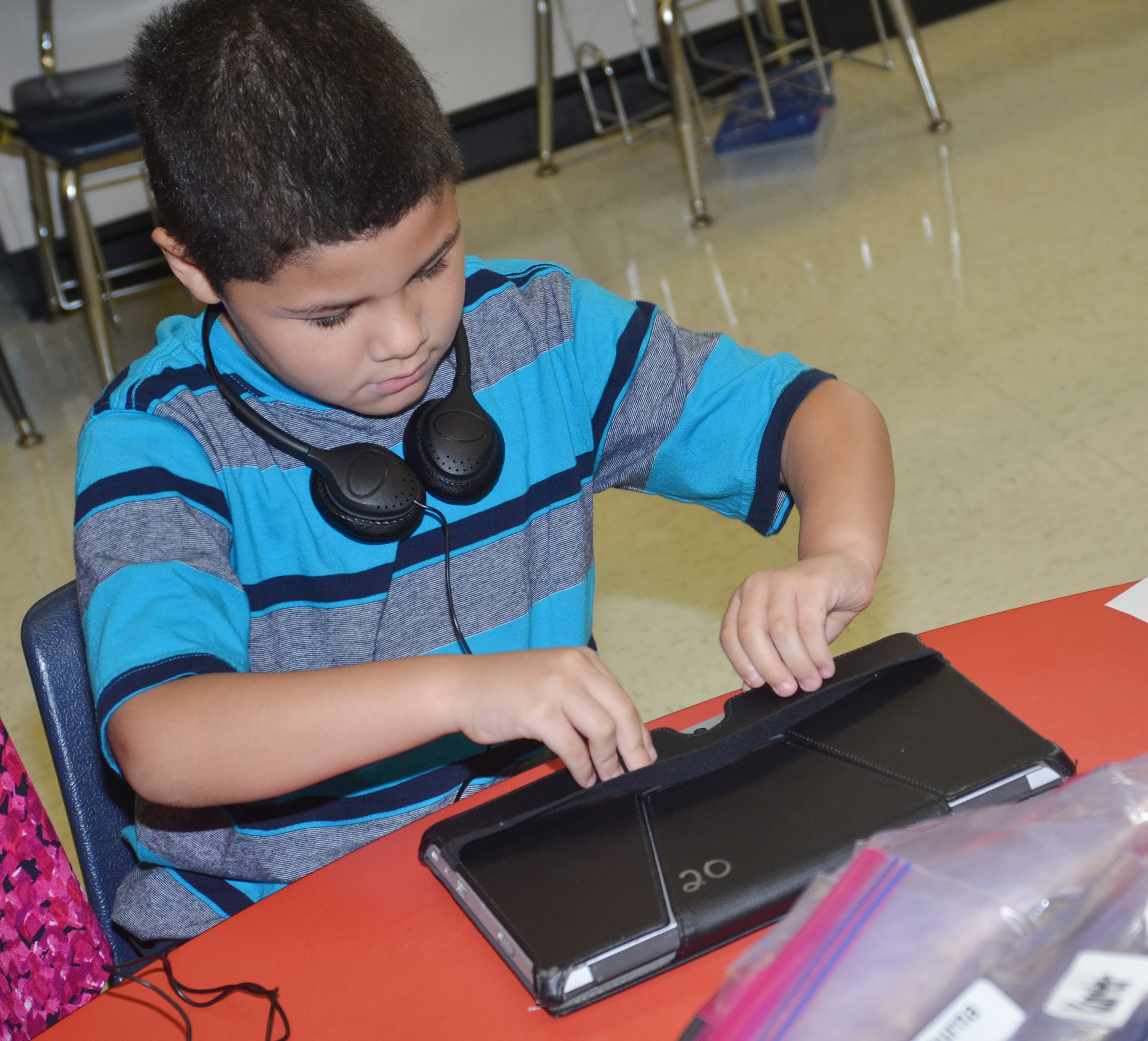 CES first-grader NyJah Vaught opens his tablet.