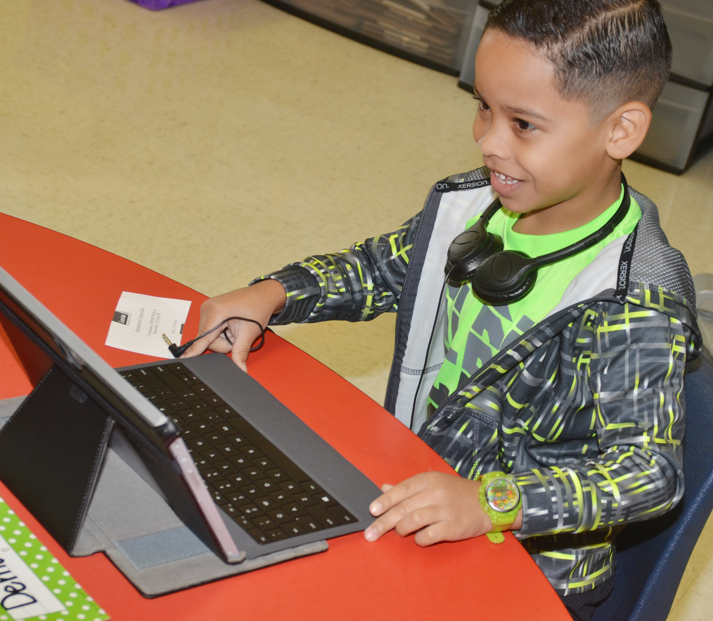 CES first-grader Demarcus Noyola smiles as he turns on his tablet.