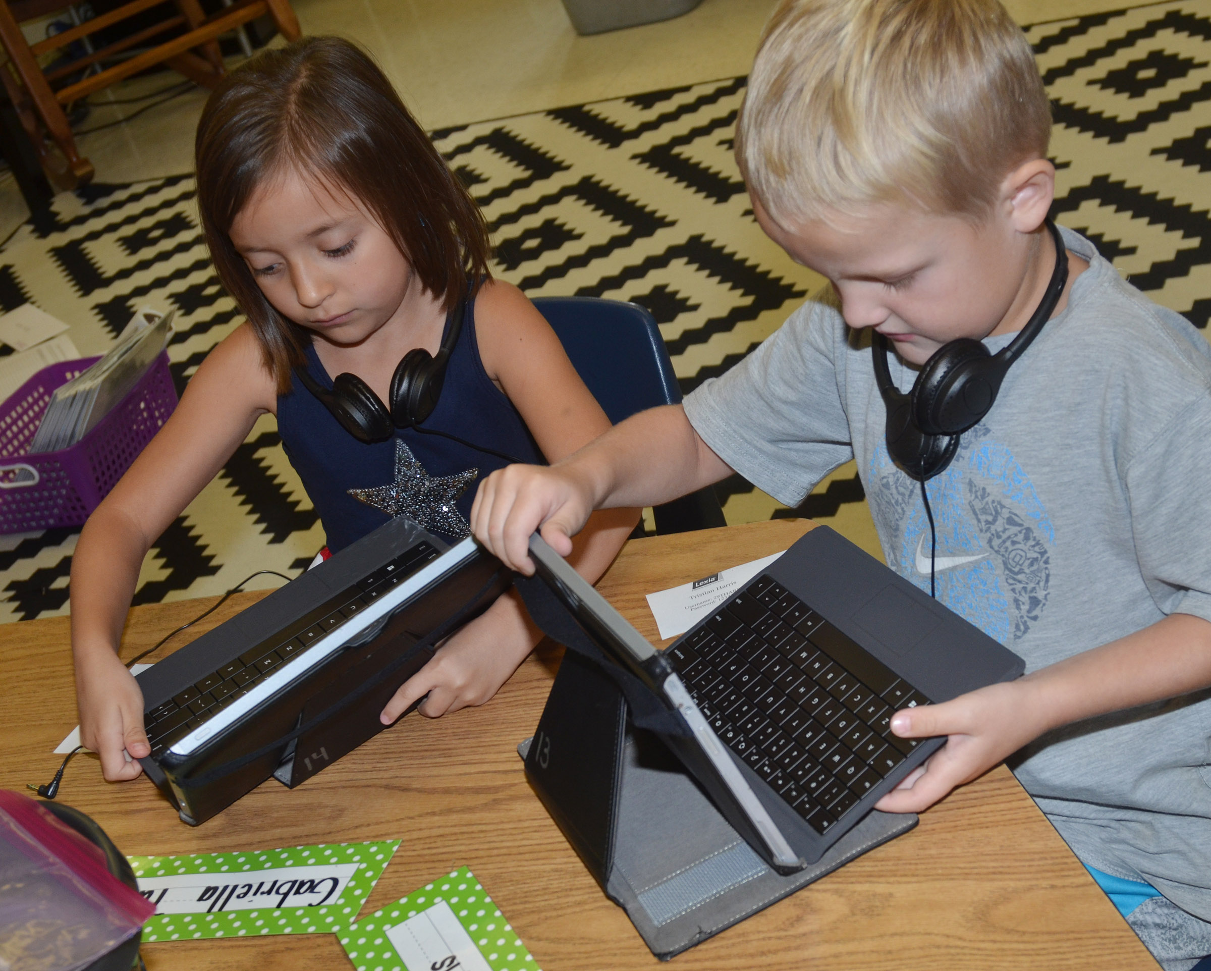 CES first-graders Gabriella Tate, at left, and Tristian Harris open their tablets.