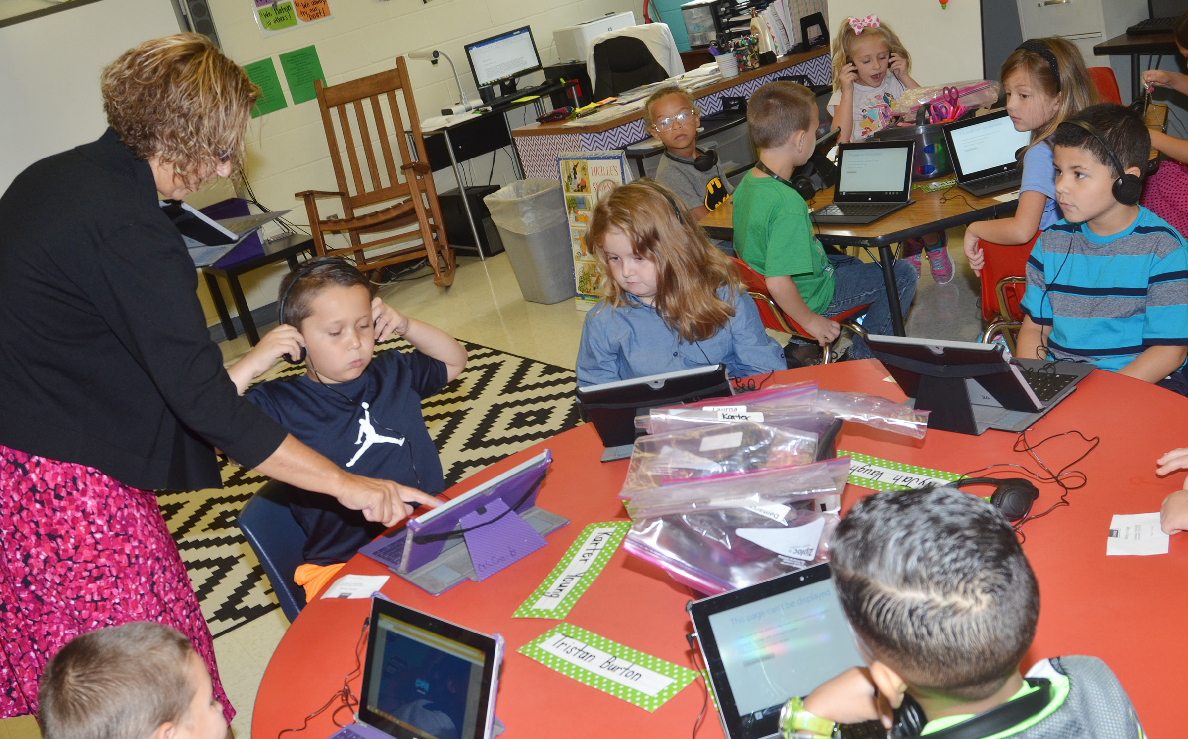 CES teacher Beverly Knifley helps first-graders turn on their tablets.