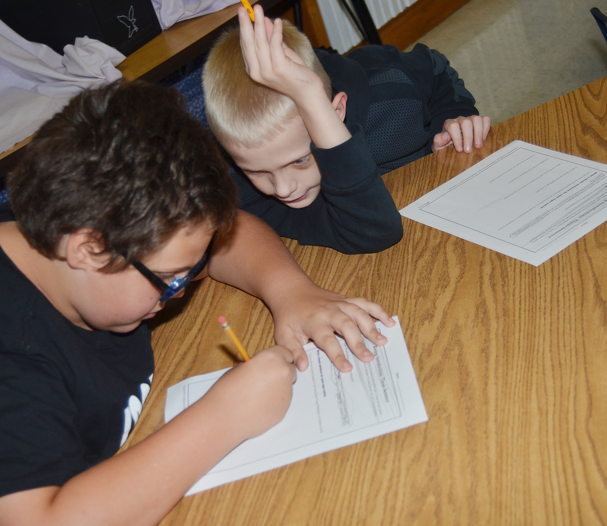 CES fifth-graders Landon Arnett, at left, and Bronson Cox talk as they write their thesis statements.