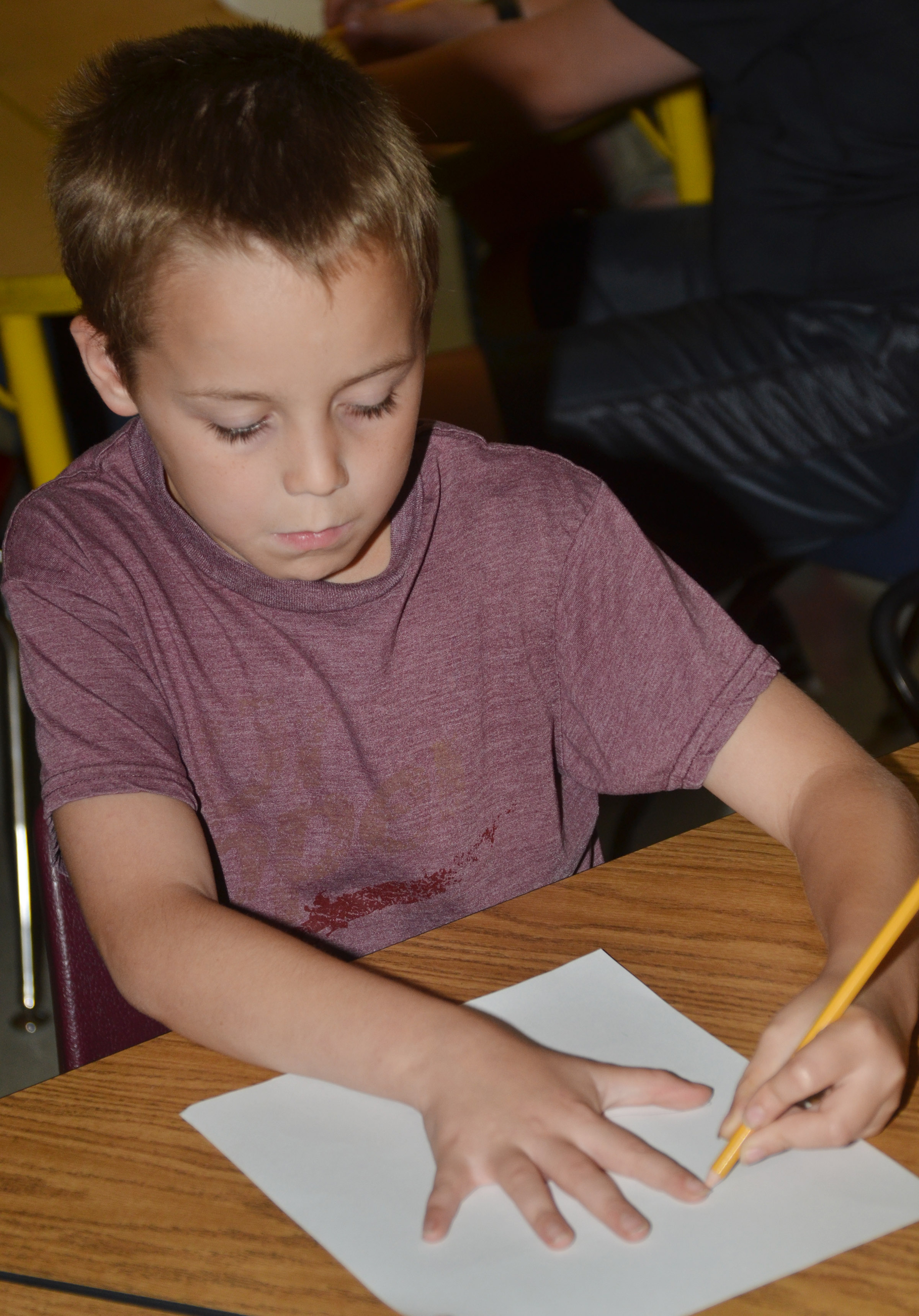 CES fifth-grader Spencer Bates traces his hand to write five topics he learned about during the lesson.