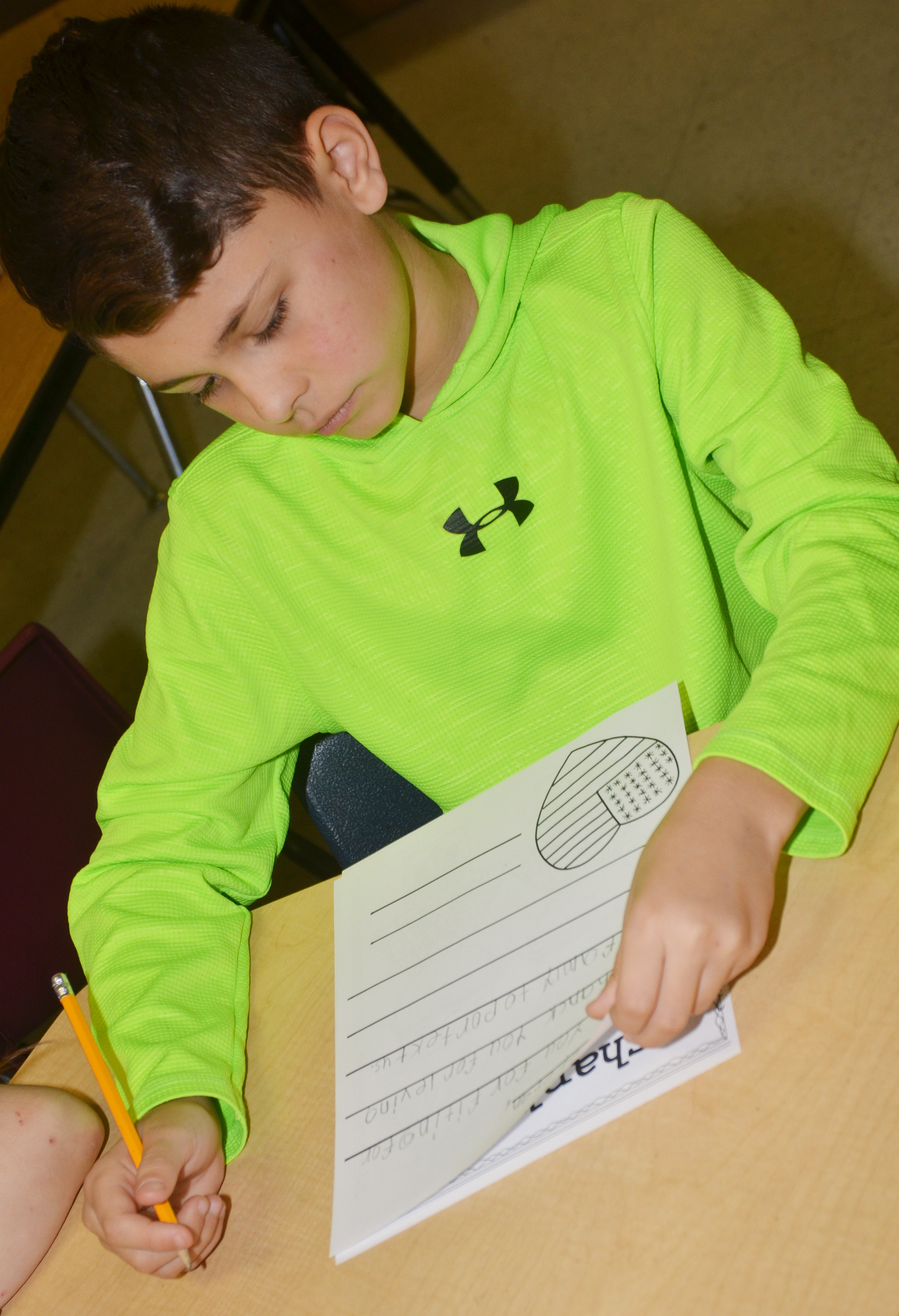 CES third-grader Braygon Noegel writes a letter to a veteran.
