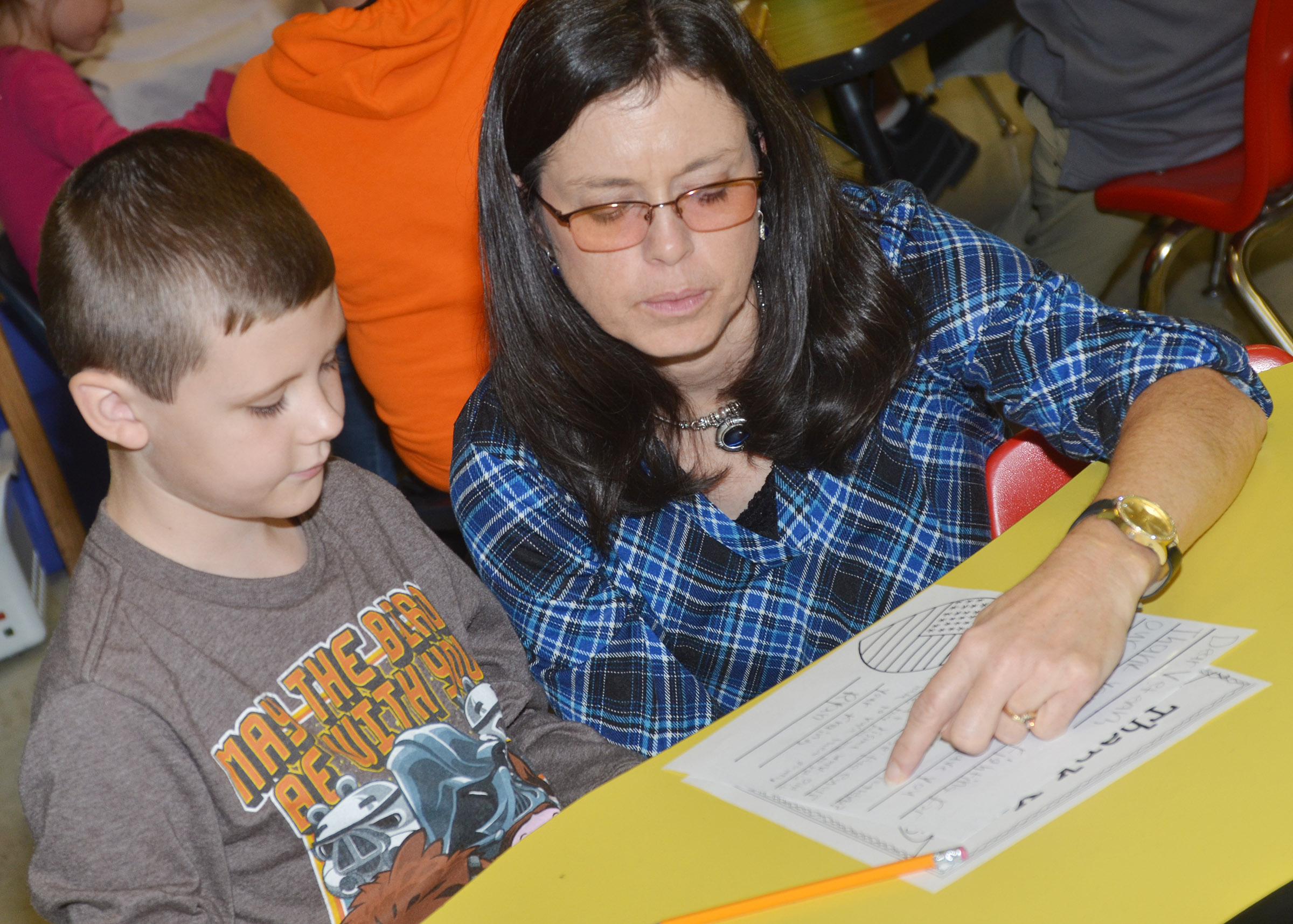 CES writing teacher Shirley Cox helps third-grader Ryan Tungate as he writes his letter to a veteran.