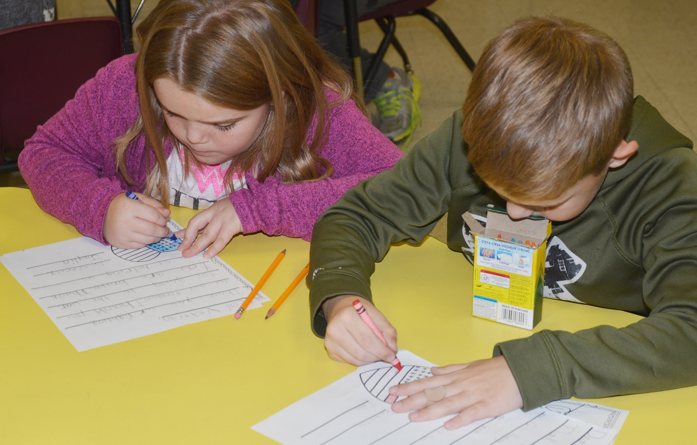 CES third-graders Jaylin Christie, at left, and Kadin Coppage color pictures on their letters to veterans.