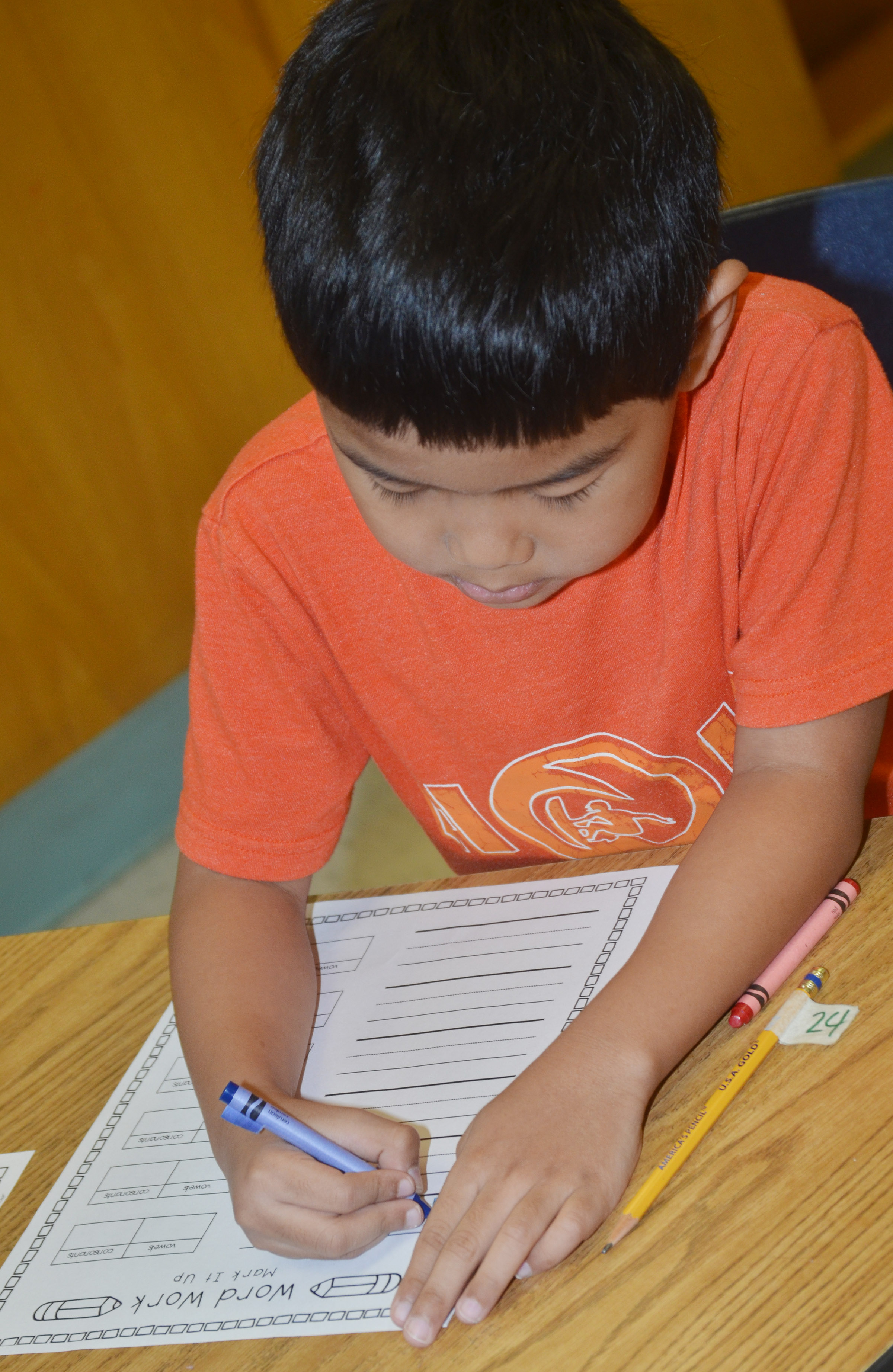 CES second-grader Zach Hak writes a vocabulary word, using one color for the consonants and another for the vowels.