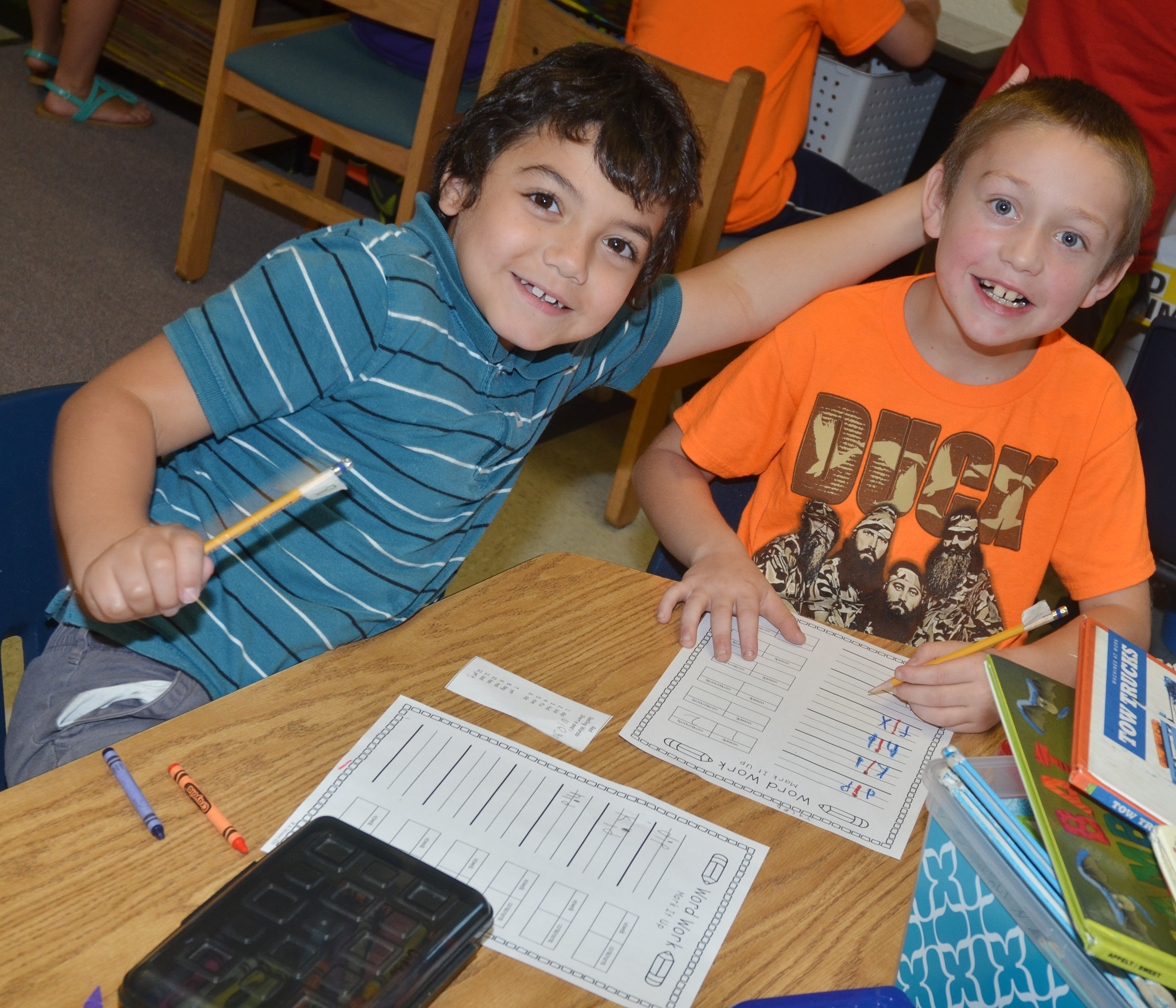 CES second-graders Diego Aquino, at left, and Jacob Golden smile for the camera as they write their vocabulary words.