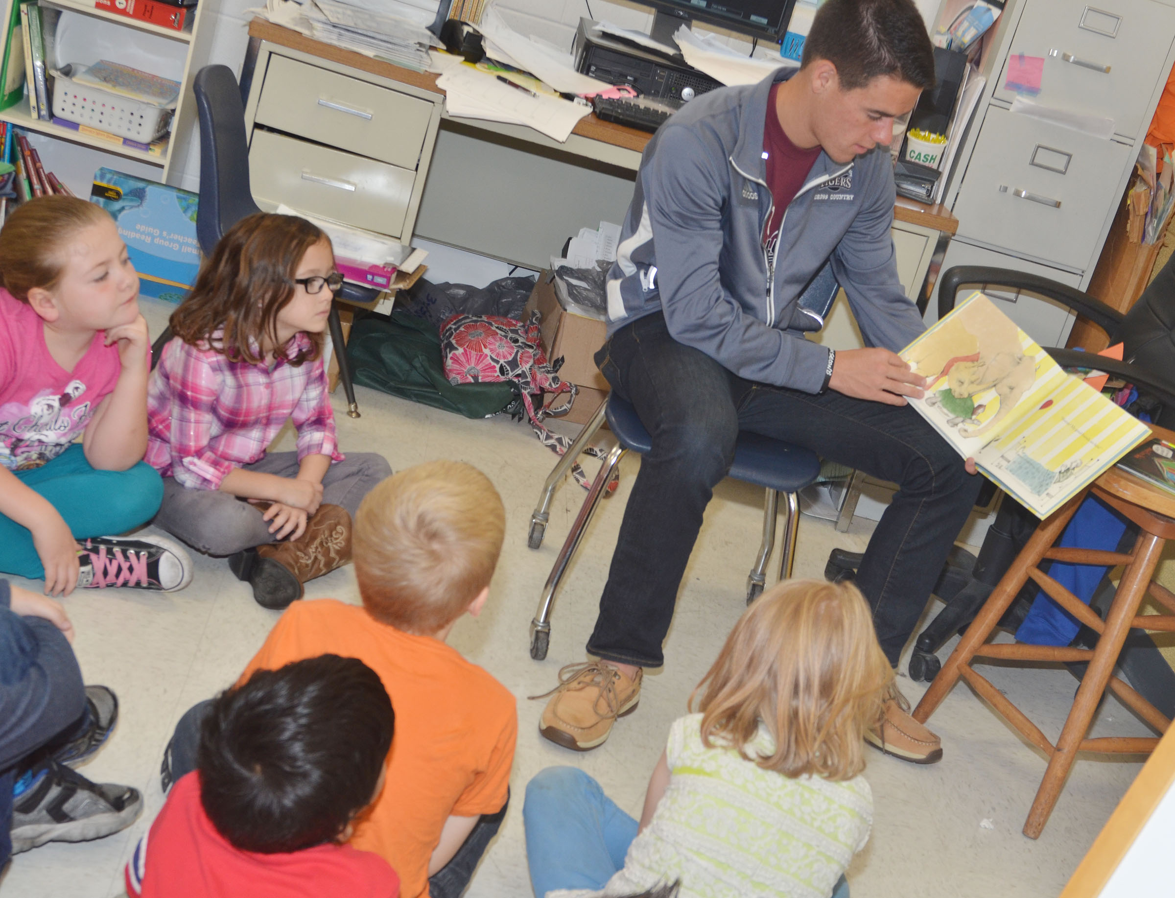 CU cross country runner Corbin Harris reads to CES first-graders.