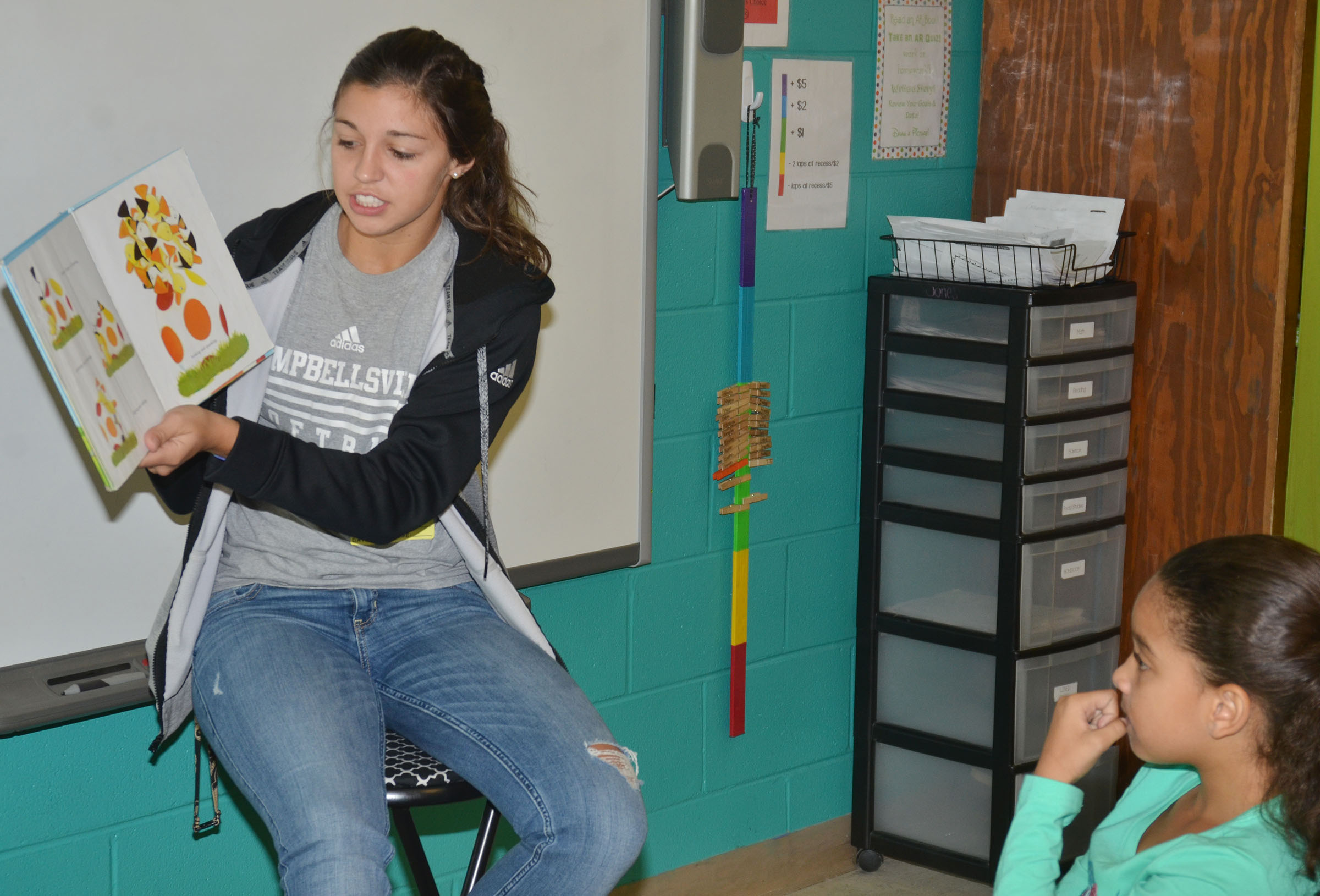 CU softball player Kalin Bottoms reads to CES third-graders.