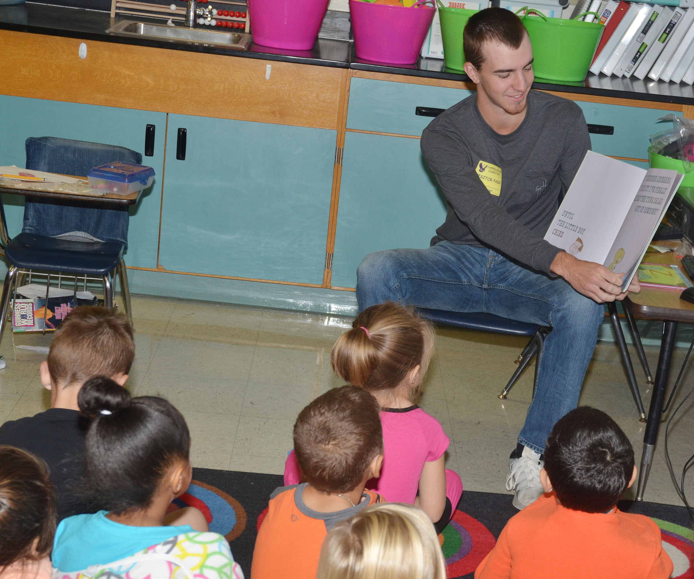 CU golf player Andrew Scalos reads to CES first-graders.