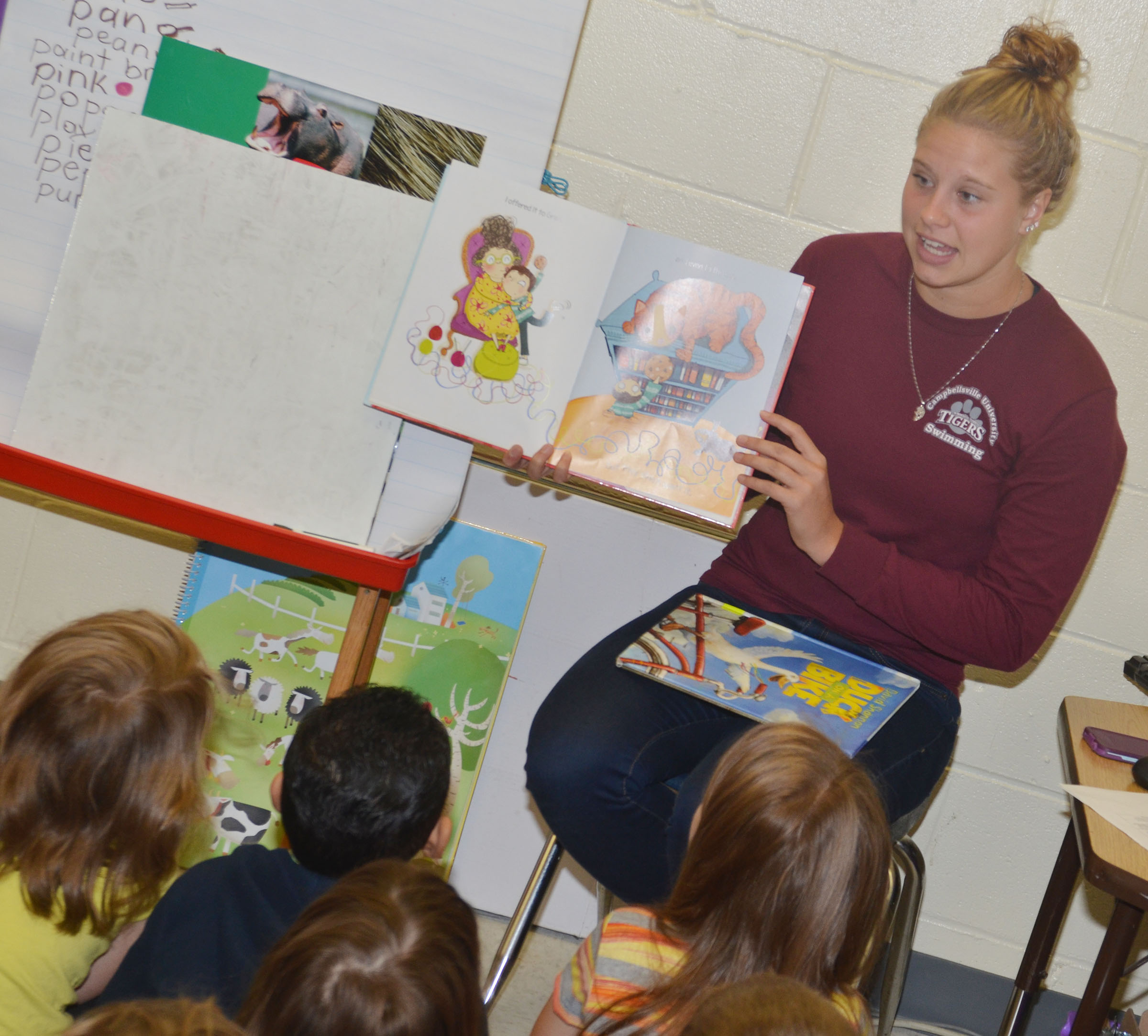 CU swimmer Jessica Cook reads to CES kindergarteners.