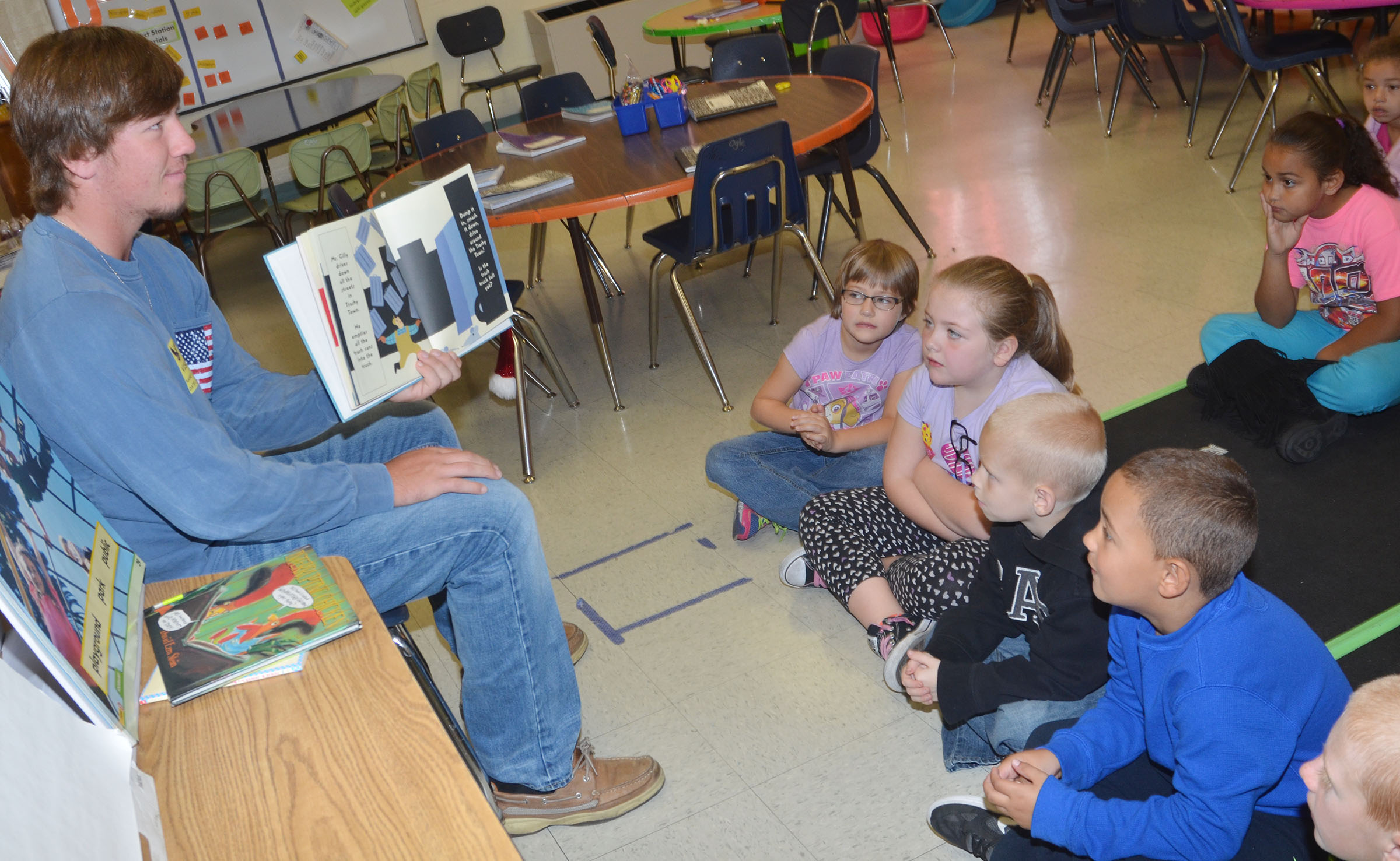 CU golf player Justin Warman reads to CES first-graders.