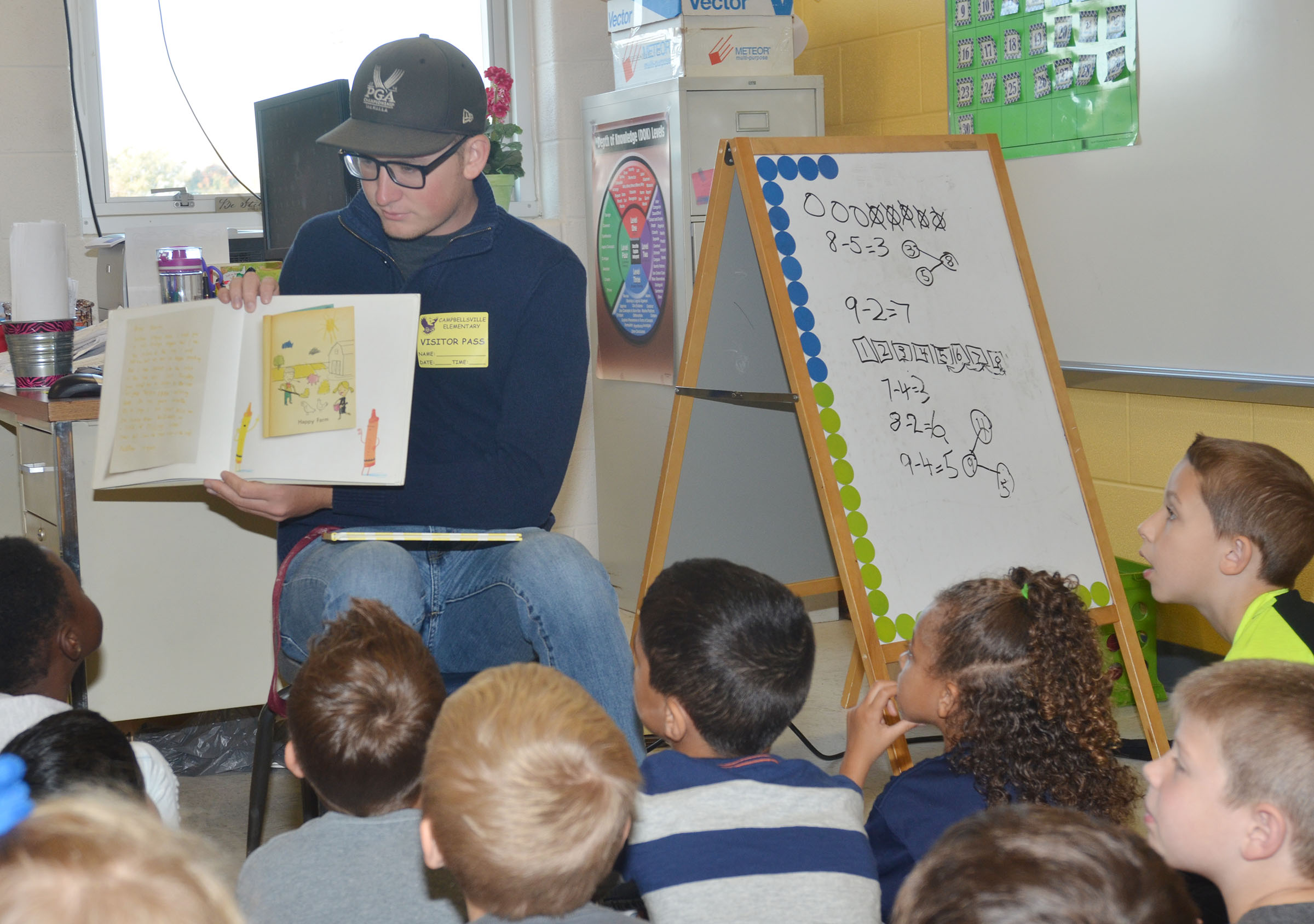 CU golf player Tristan Blevins reads to CES first-graders.