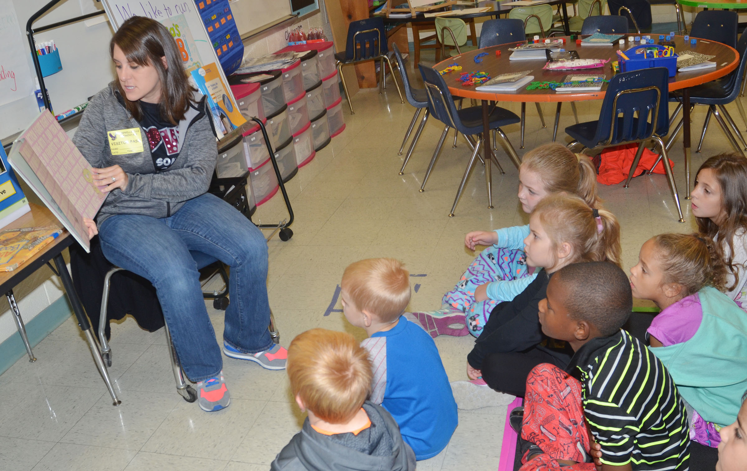 CU golf assistant coach Lauren Willis reads to CES first-graders.