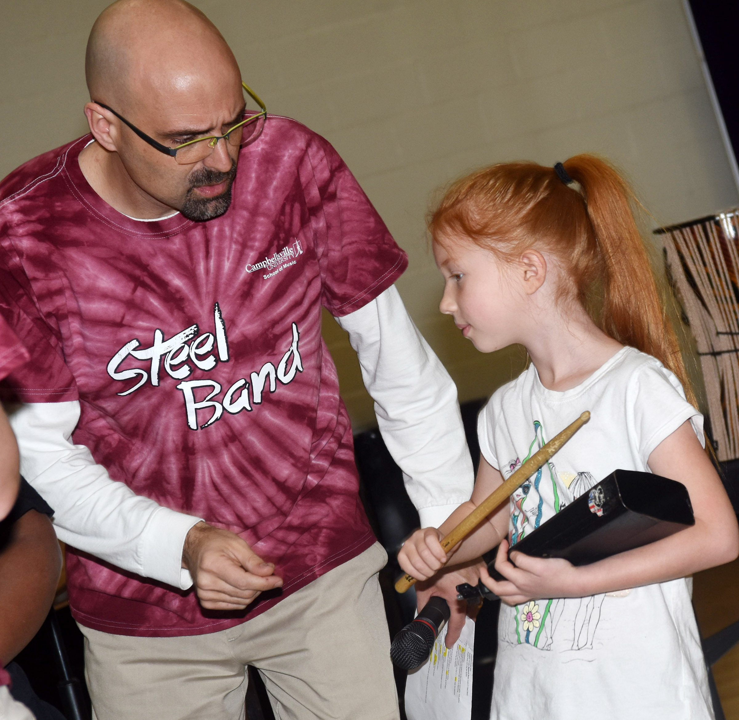 Dr. Chad Floyd, associate professor of percussion at CU, helps CES first-grader Bella Stout play a rhythm.