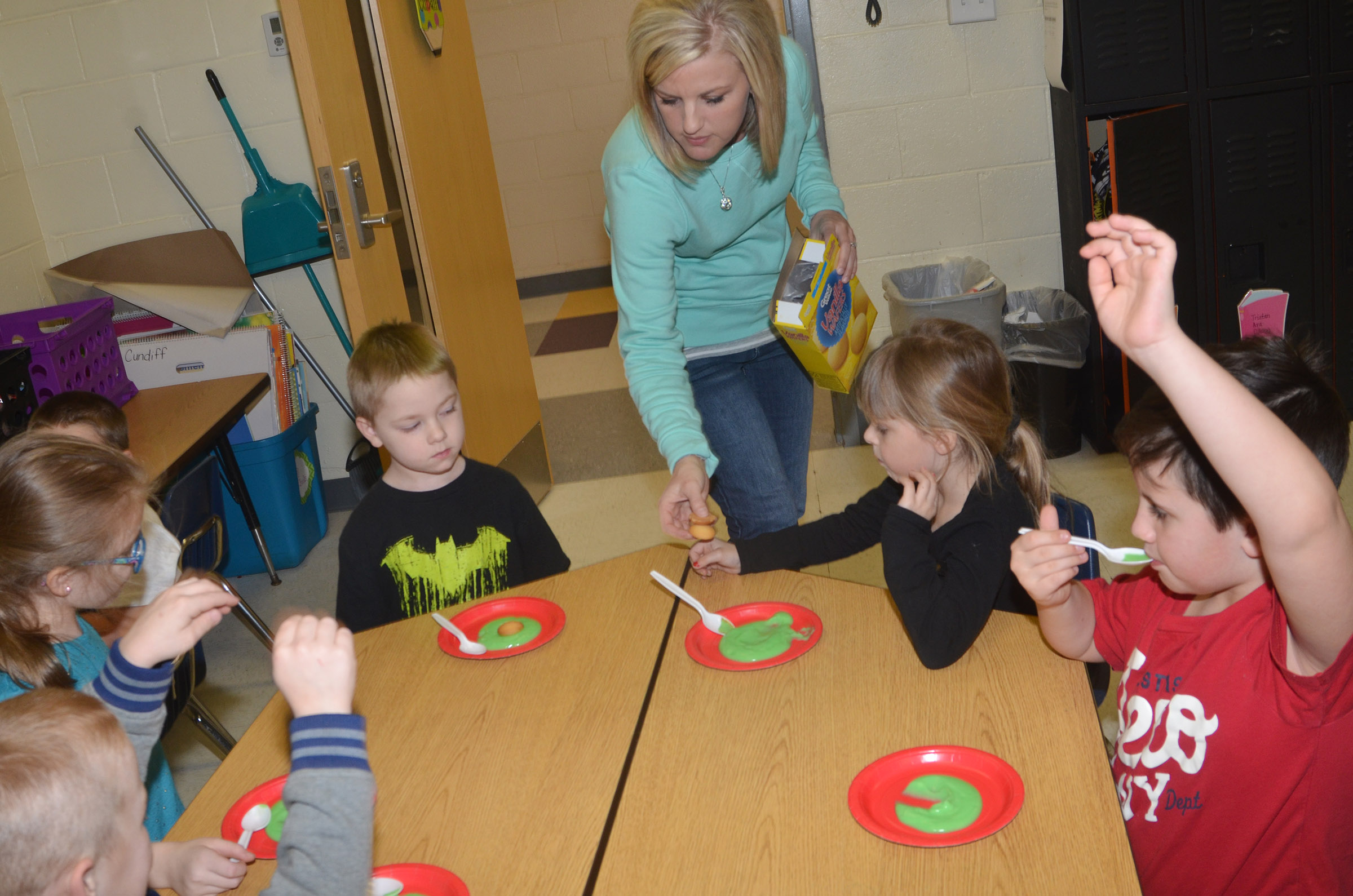 CES kindergarten teacher Leanna Cundiff passes out vanilla wafers to her students.