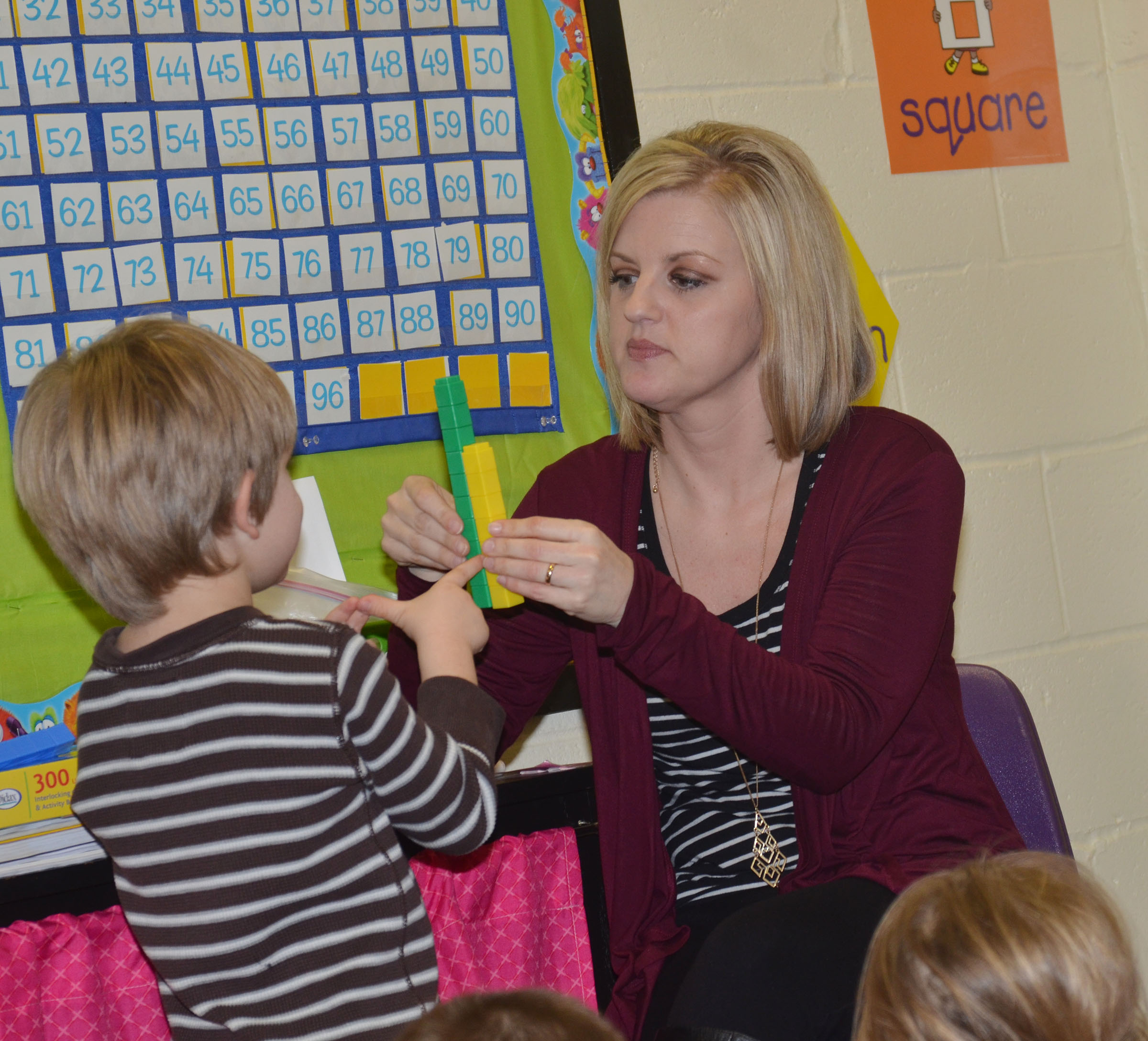 CES kindergarten teacher Leanna Cundiff asks student Luke Banta which tower is smaller, and by how many blocks.