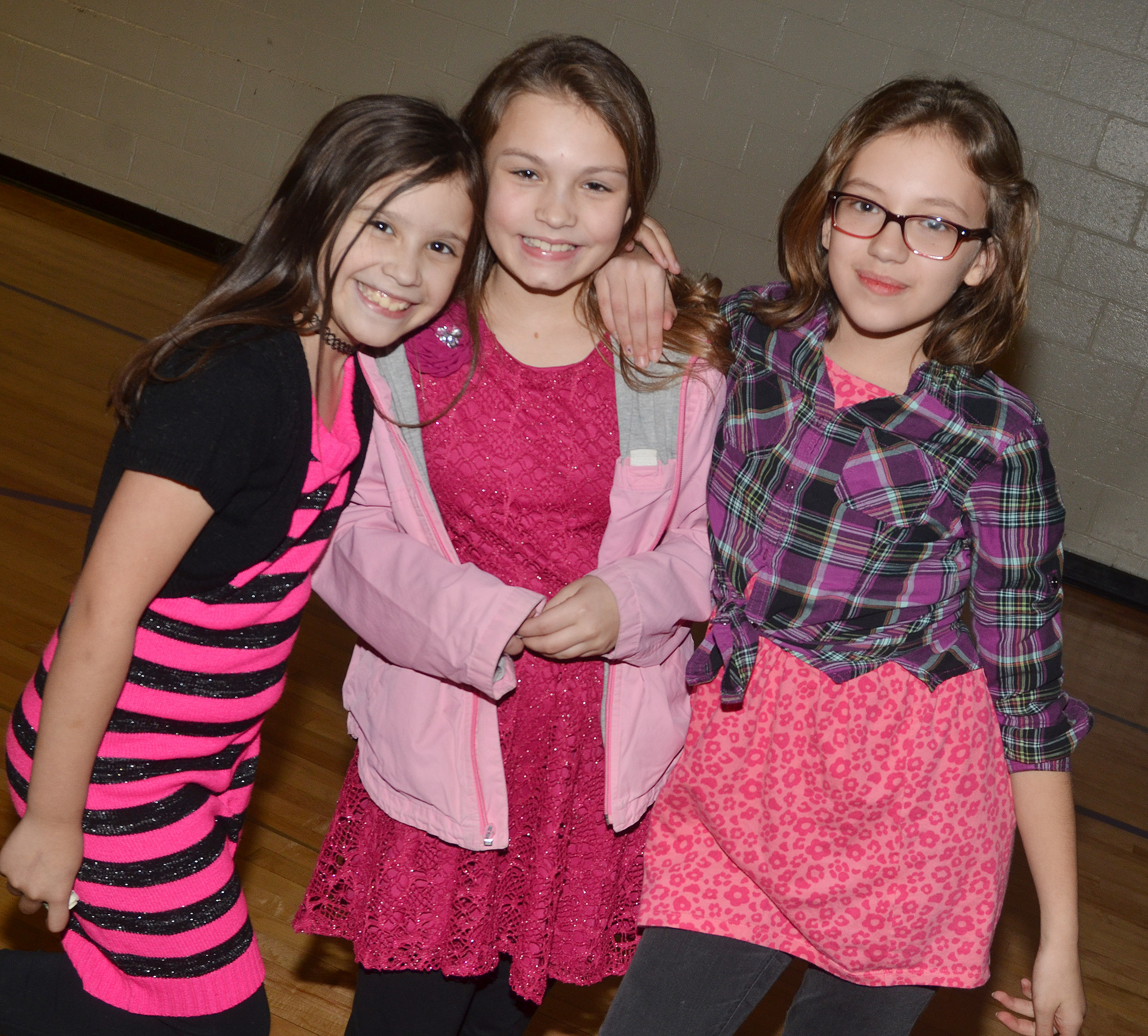 From left, CES fourth-graders Zehavah Negron, Kealey Mann and Trinity McFarland smile at the dance.