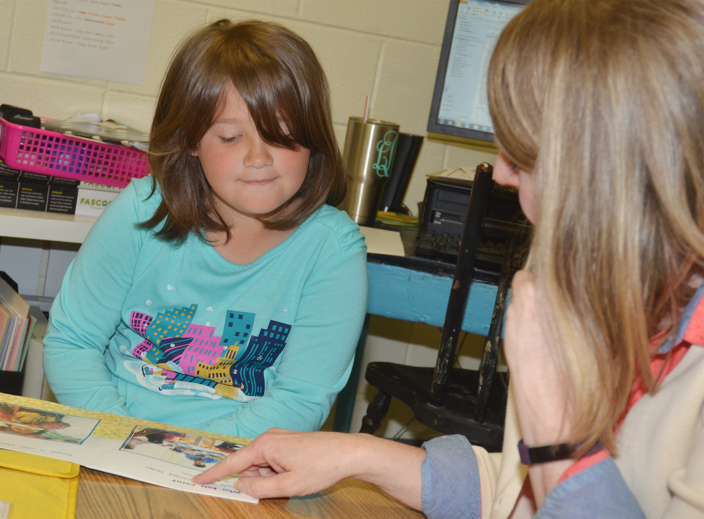 CES teacher Laura Dicken reads with first-grader Destiny Rhinehart.