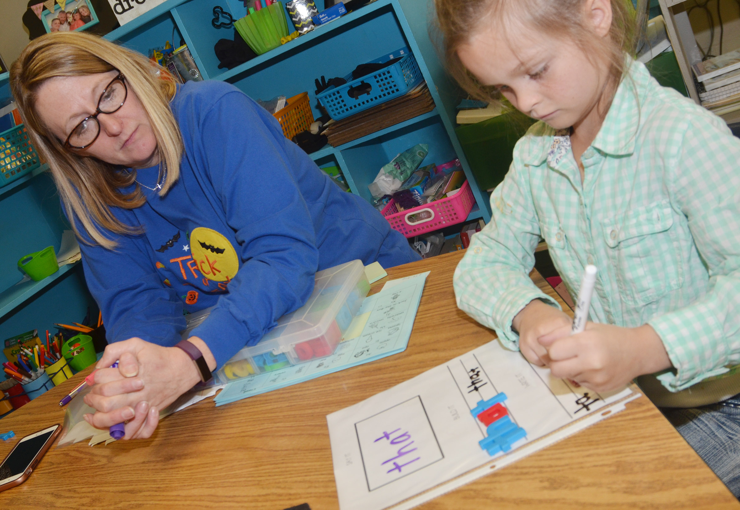 "CES reading interventionist Laura Dicken watches as first-grader Addison Perkins writes the word ""that."""