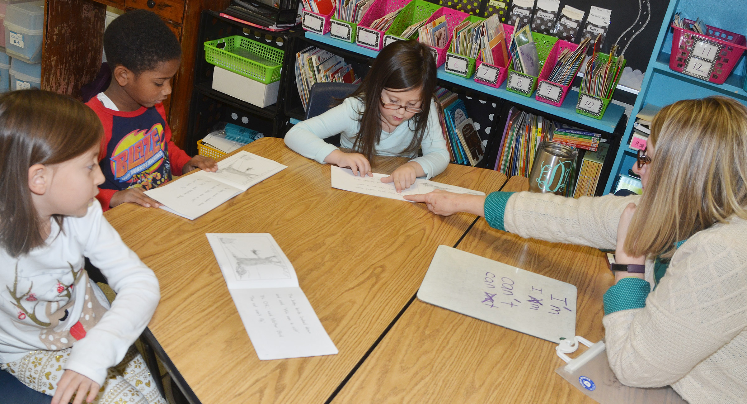 CES reading interventionist Laura Dicken works with CES first-graders, from left, Gabriella Tate, Kasen Smith and Trinity Clark as they practice reading contractions.
