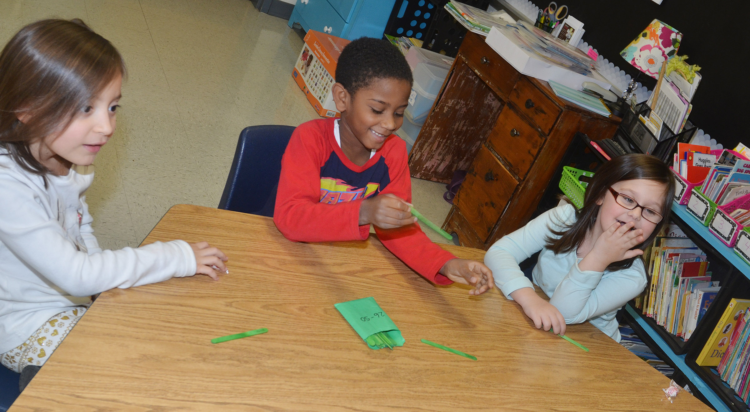 From left, CES first-graders Gabriella Tate, Kasen Smith and Trinity Clark play a word game together.