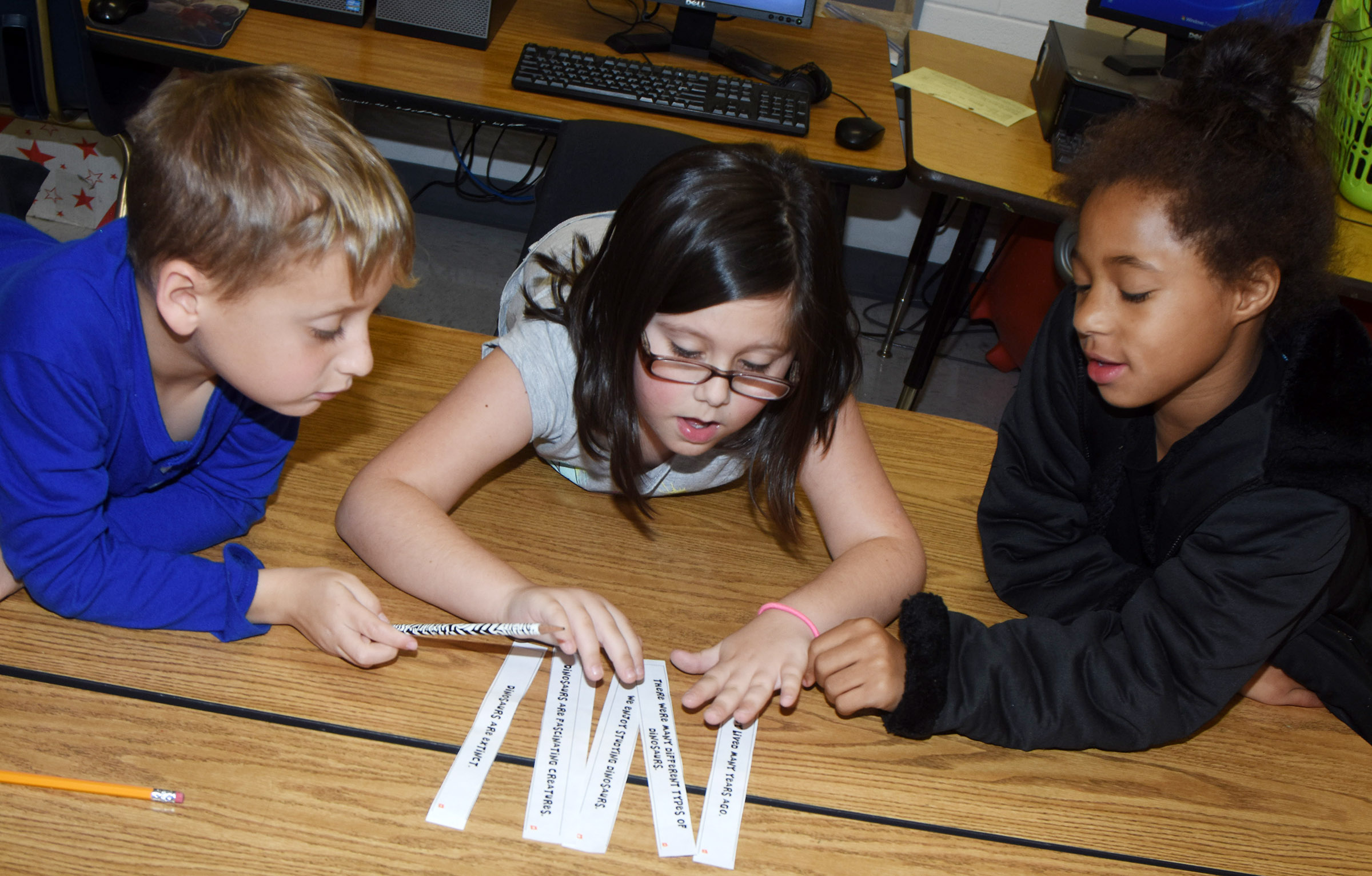 From left, CES second-graders Gavin Paris, Trinity Clark and Brea Miller work to put their paragraph sentences in the correct order.