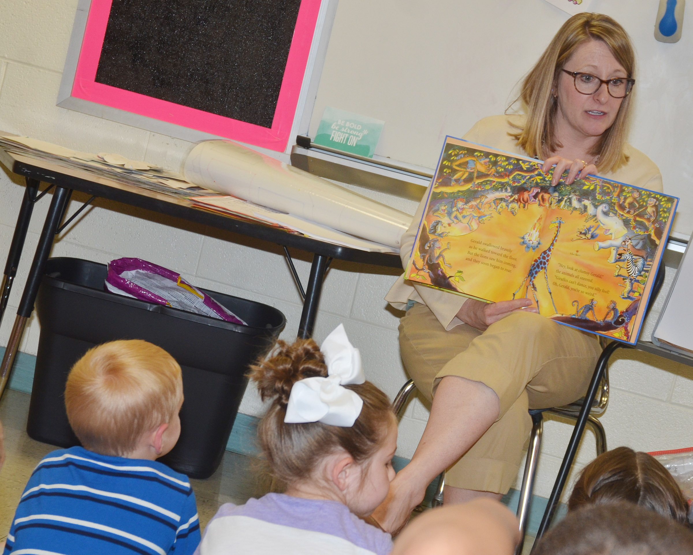 "CES reading interventionist Laura Dicken reads ""Giraffes Can't Dance"" to first-graders."