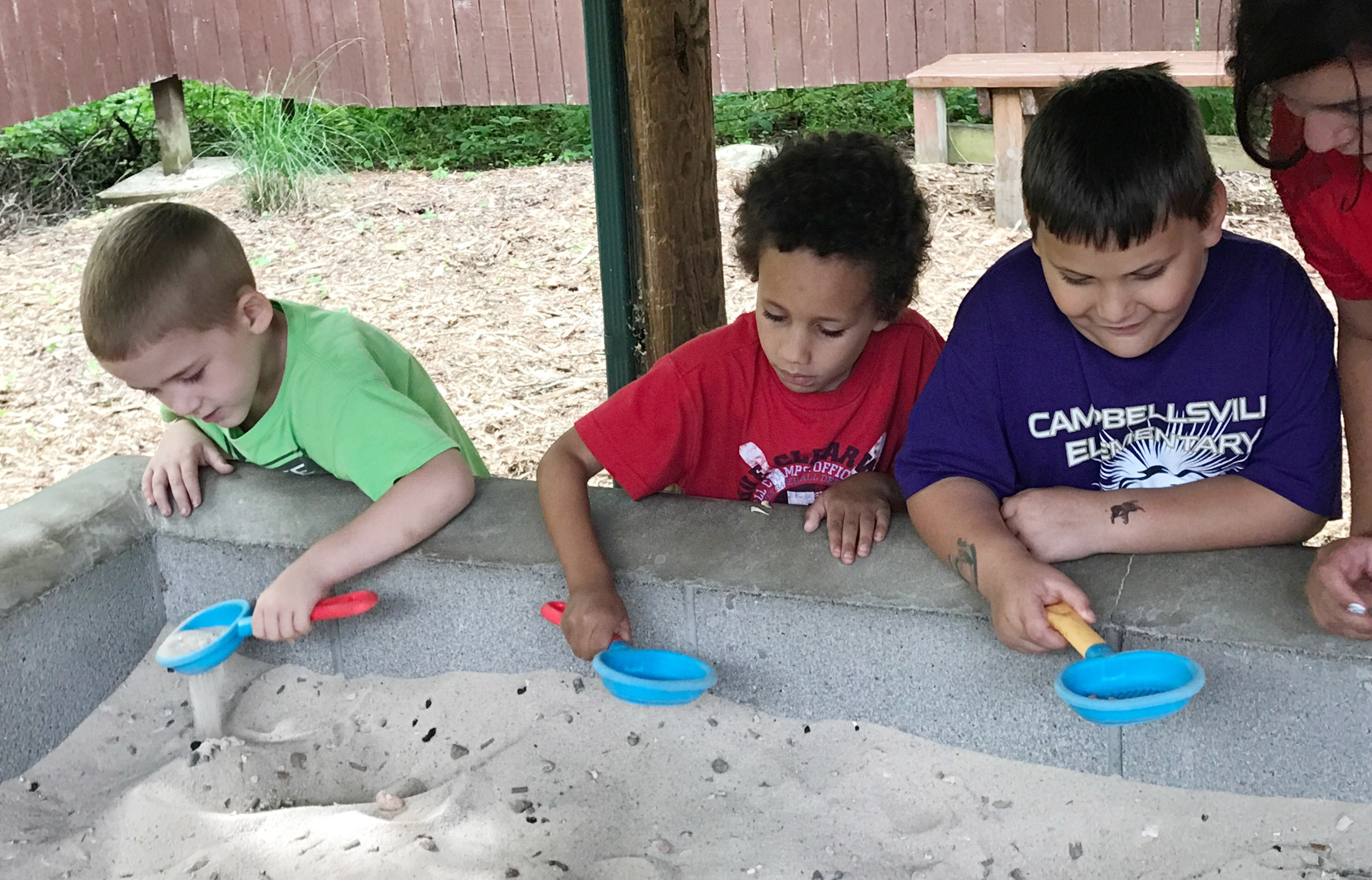 From left, CES kindergarteners Mason Edwards, Jaxon Williams and Cloud Malone dig for fossils.