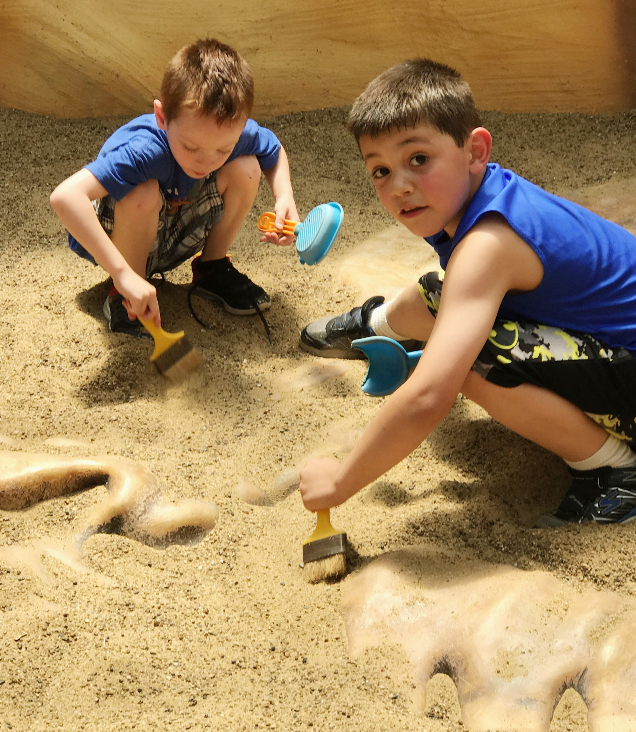 CES kindergarteners Mason Edwards, at left, and Keagan Shearer dig for fossils.